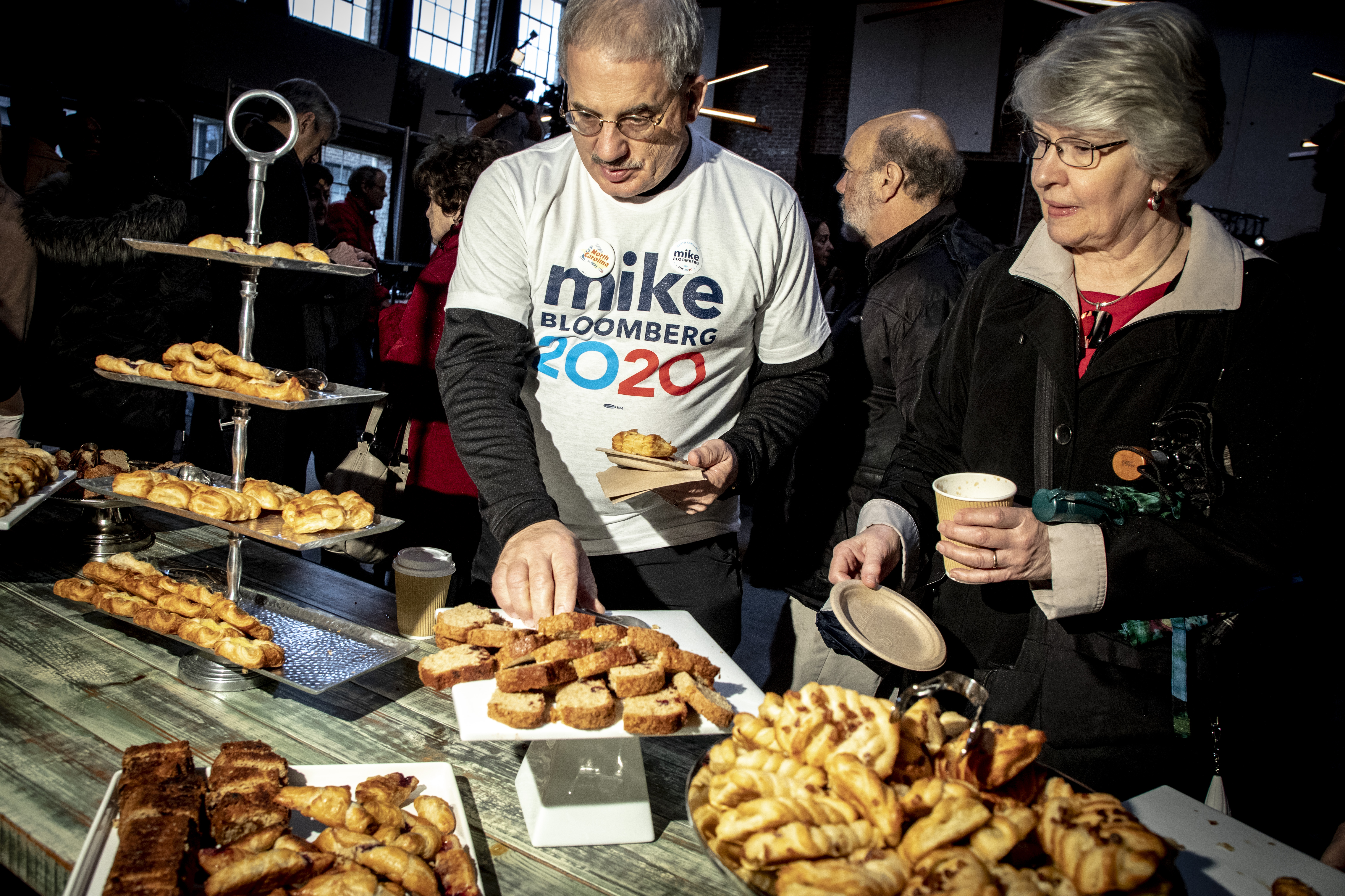 """Man and woman look like a table filled with pastries; the man wears a shirt that reads """"Mike Bloomberg 2020."""""""
