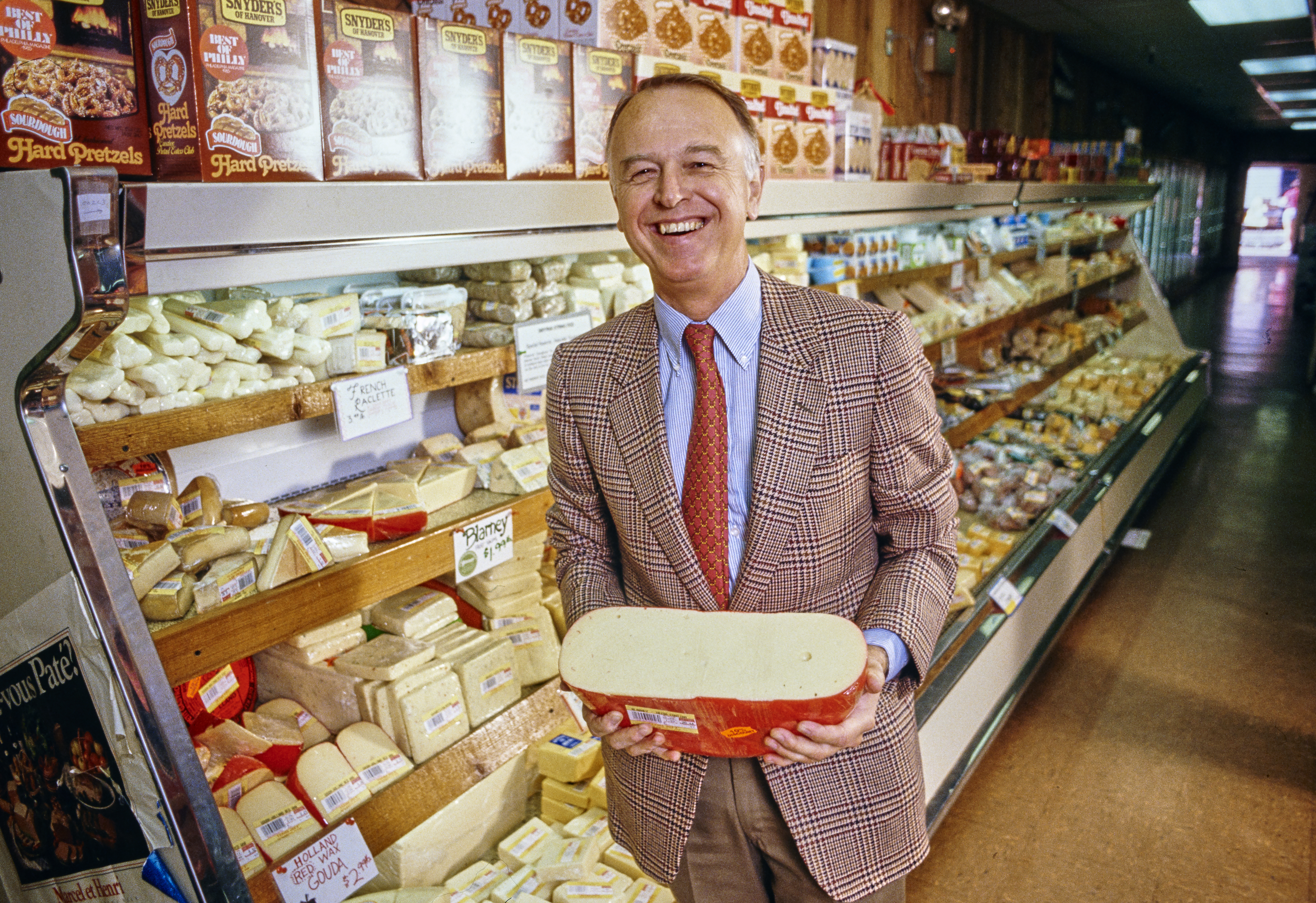 Trader Joe's founder Joe Coulombe smiling and holding a block of cheese in a store.