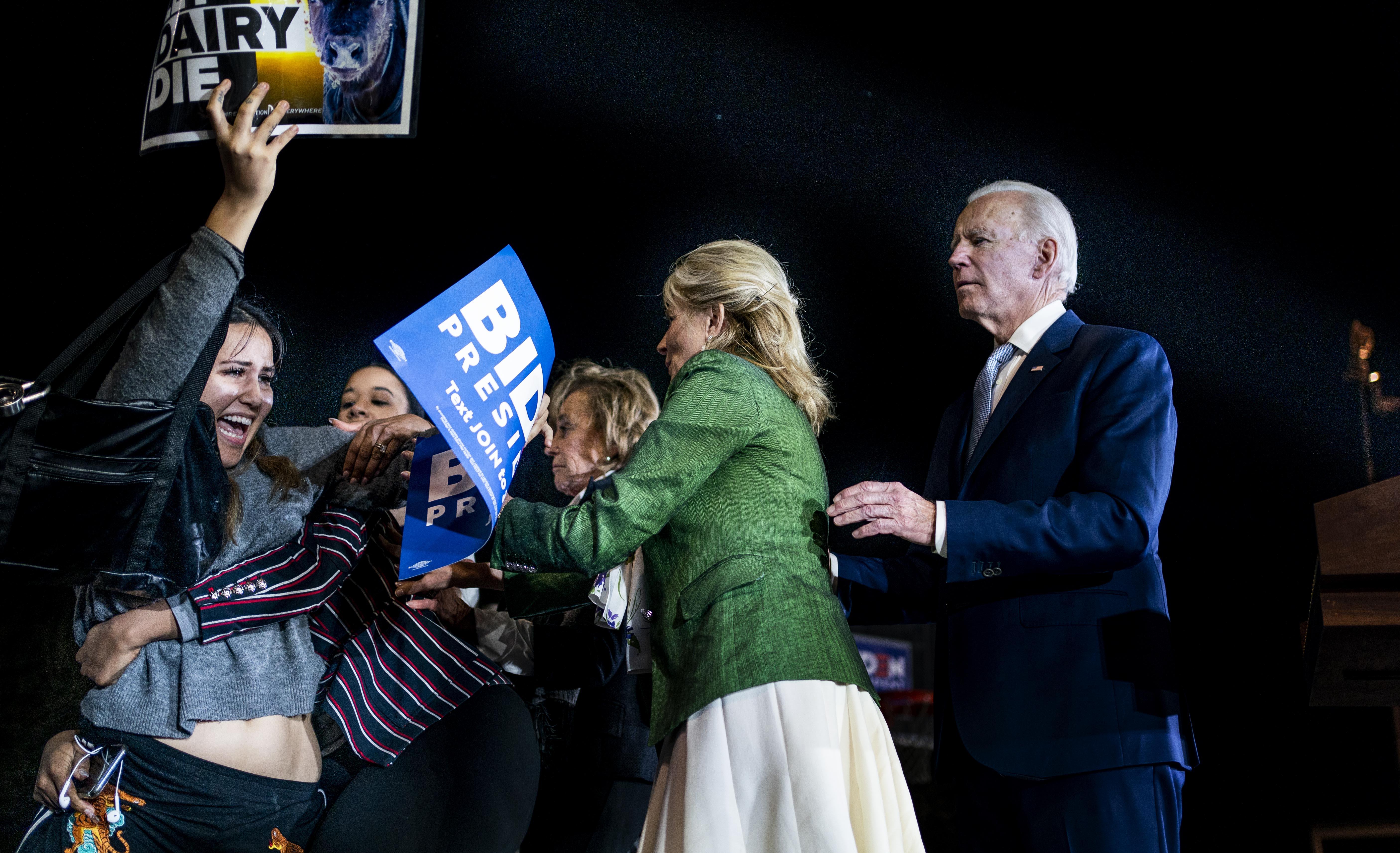 Jill Biden stands between an animal-rights protester and Joe Biden onstage.