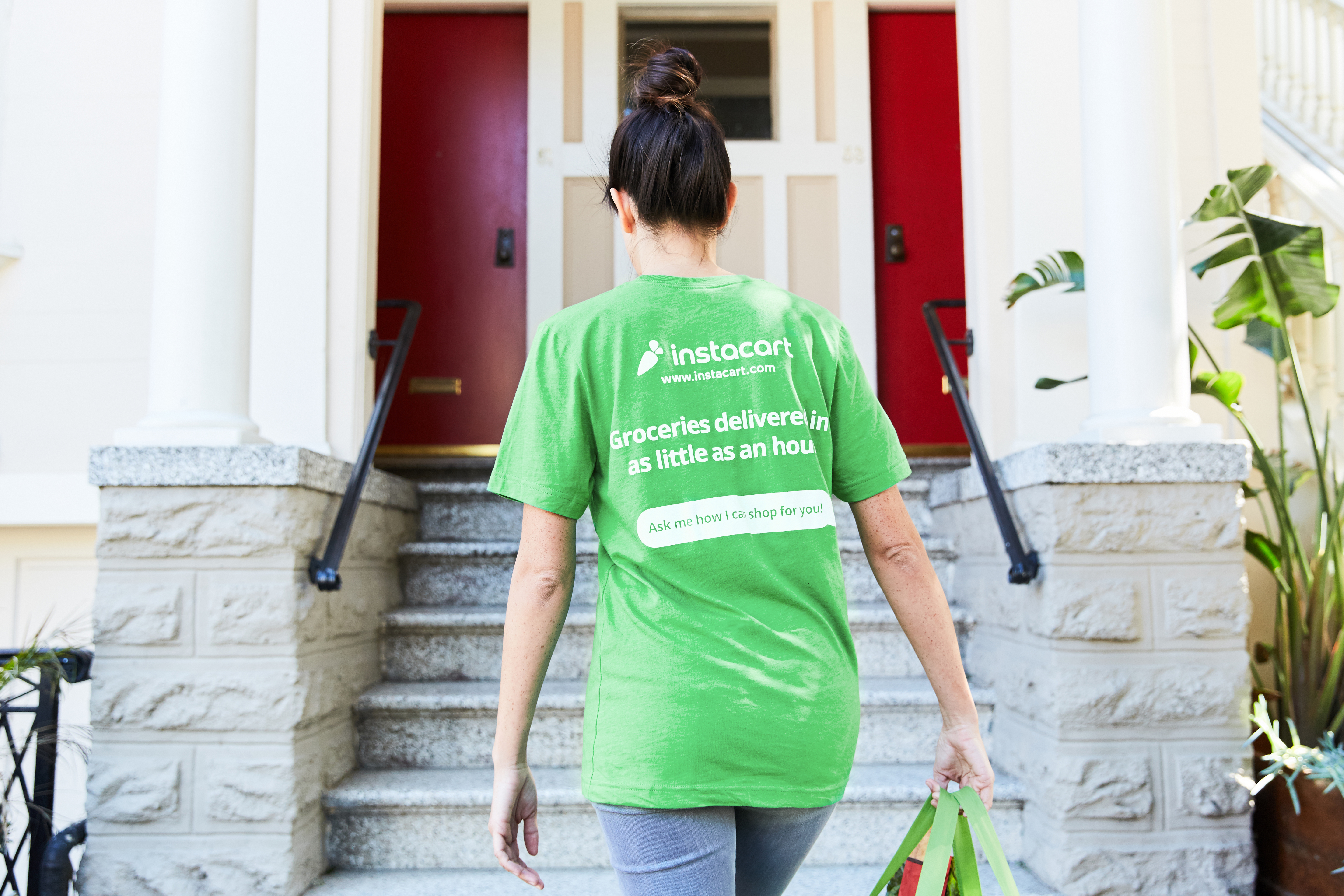 A woman in a green Instacart shirt from behind, climbing steps to a house