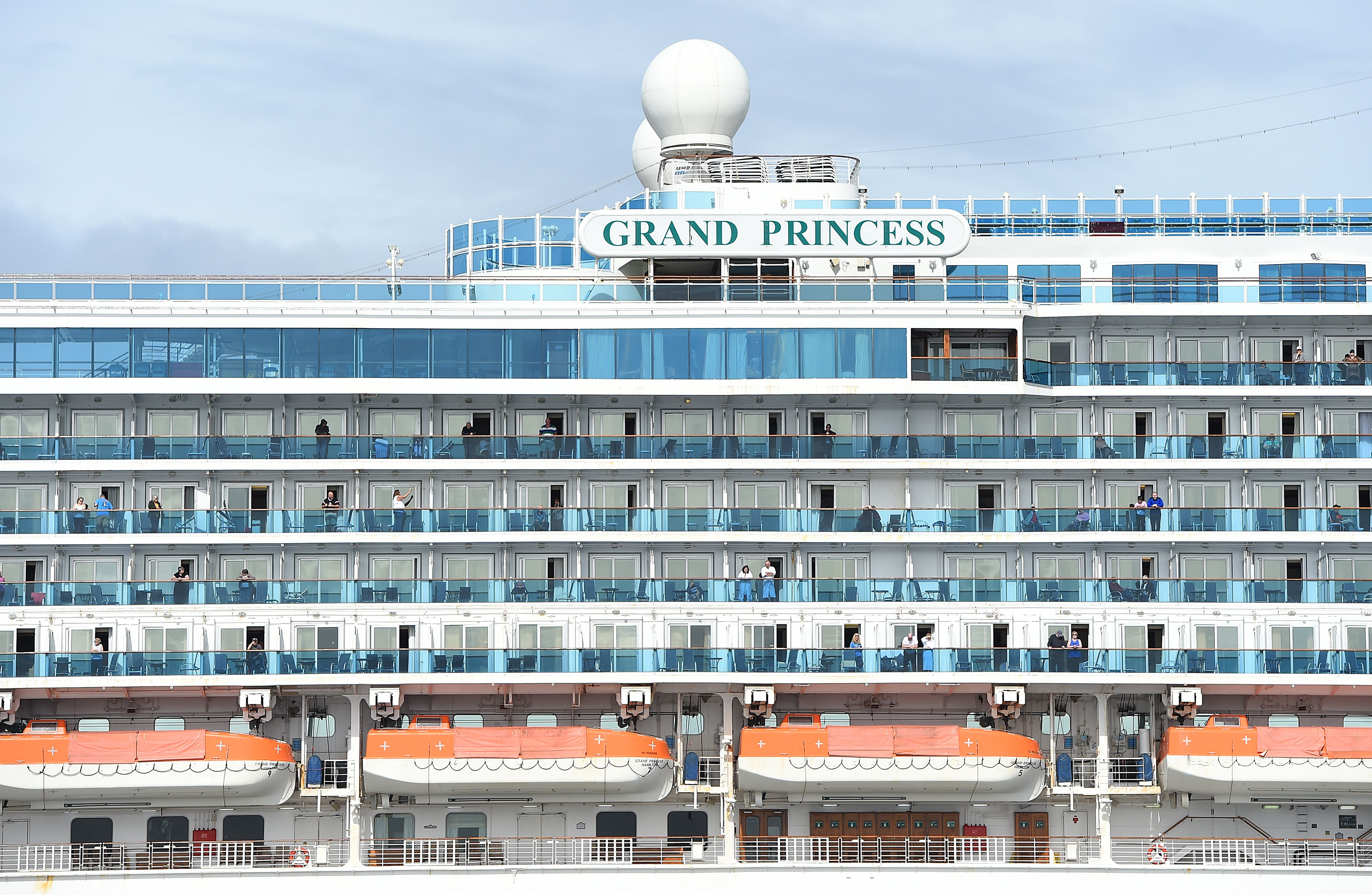 Passengers look out from aboard the Grand Princess cruise ship, operated by Princess Cruises