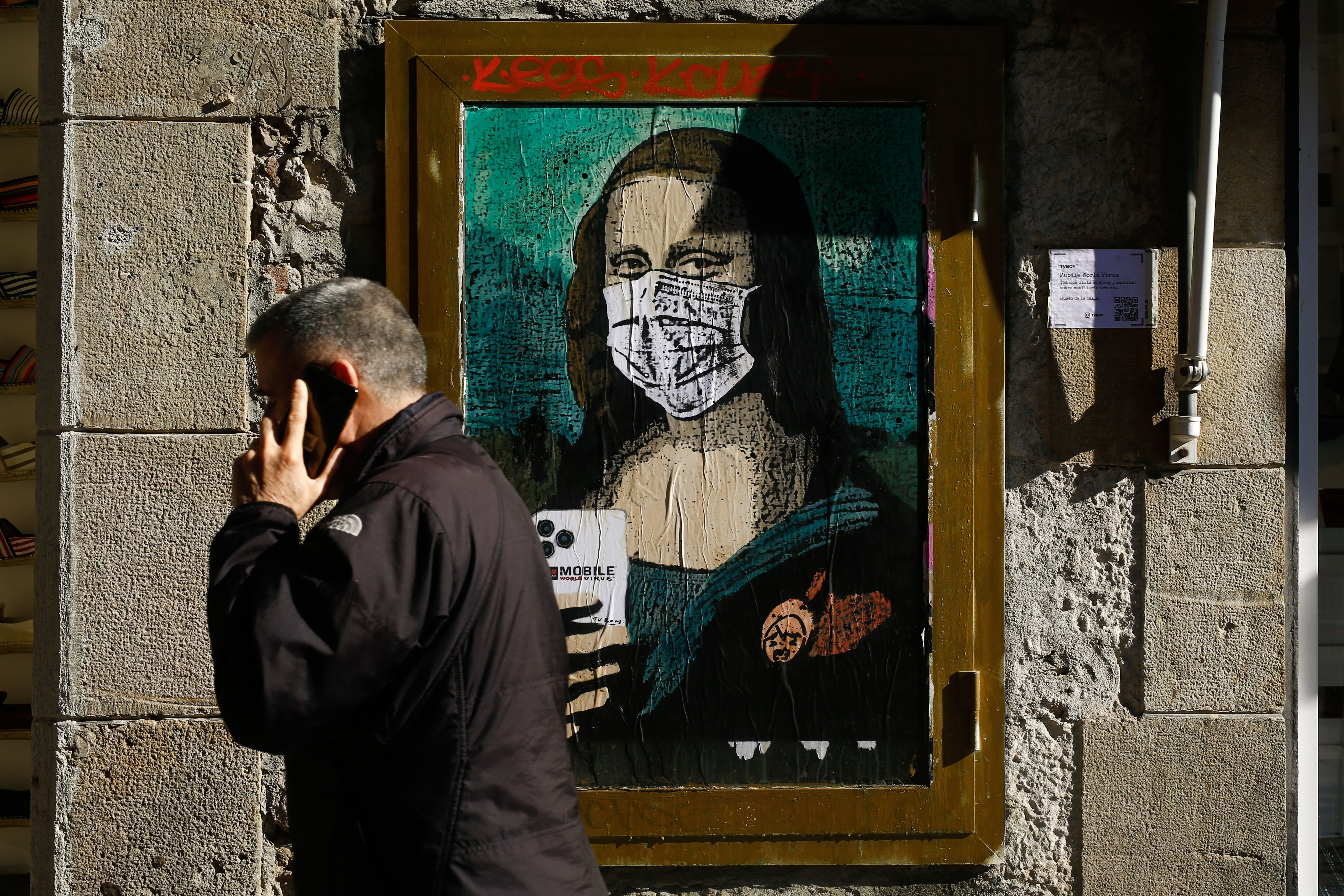 Pedestrians walk past a painting of the Mona Lisa holding a phone and wearing a breathing mask.