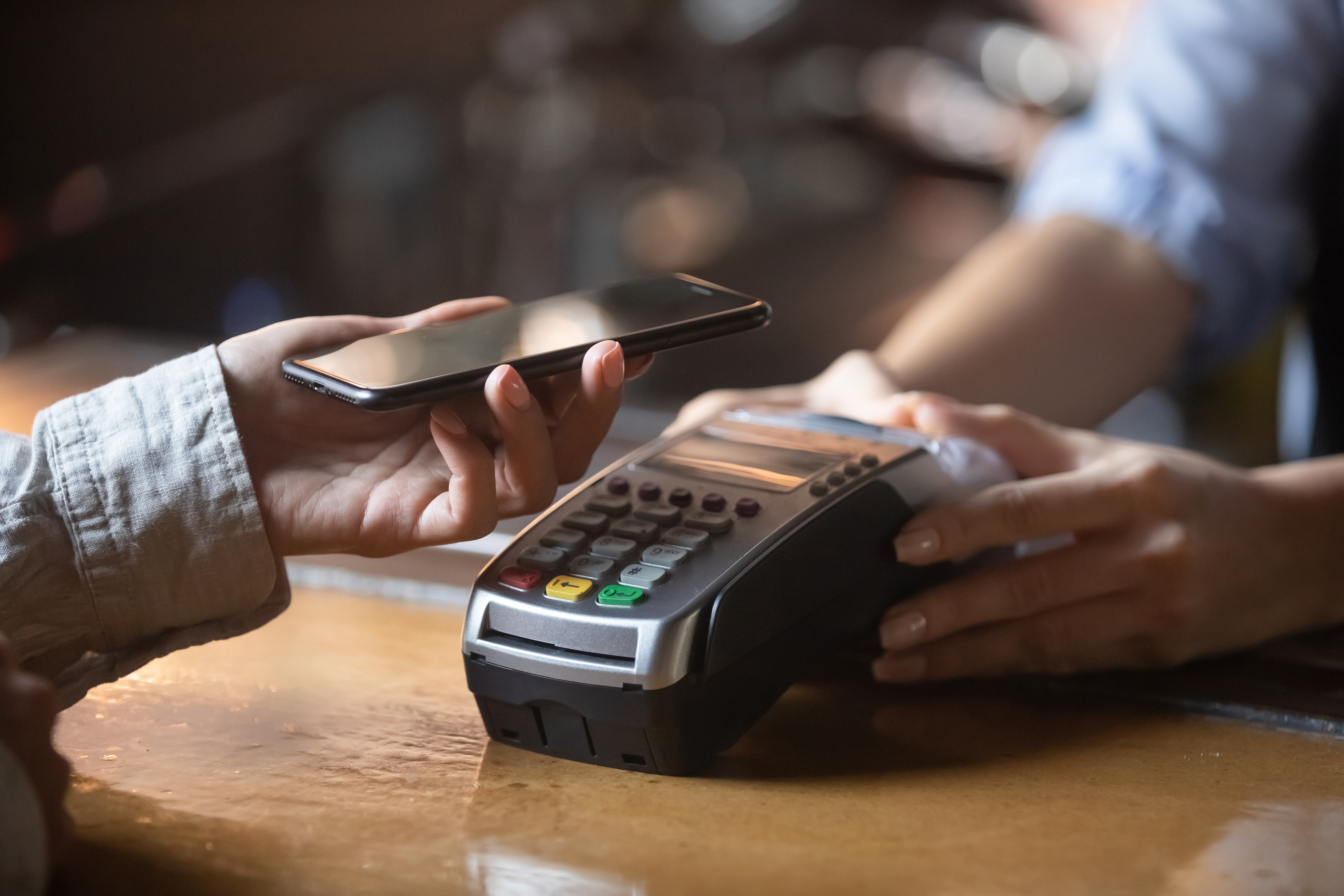 Close up of female client hold smartphone paying for order using modern easy nfc technology,