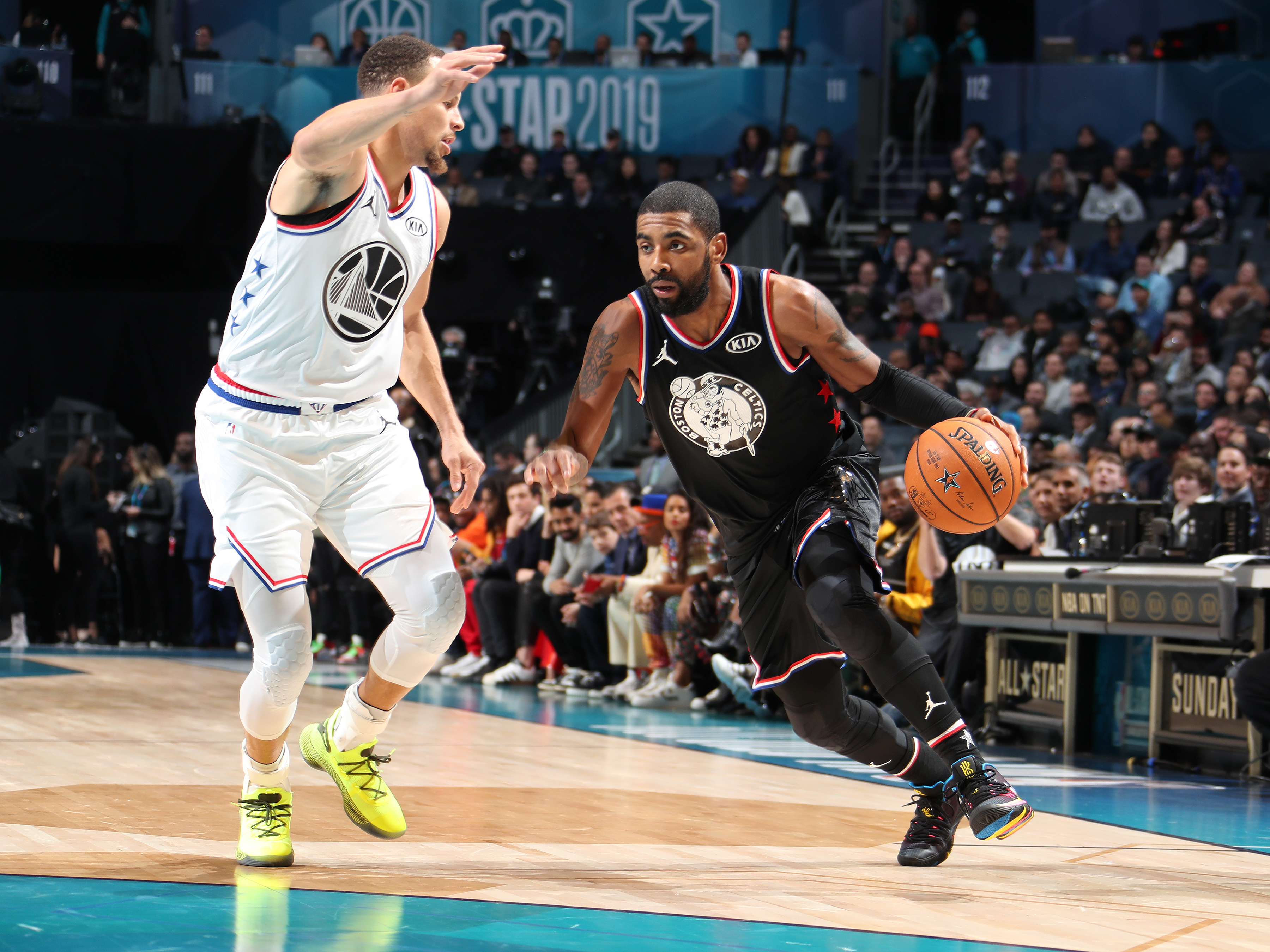 A professional basketball player dribbles past a defending member of the other team.