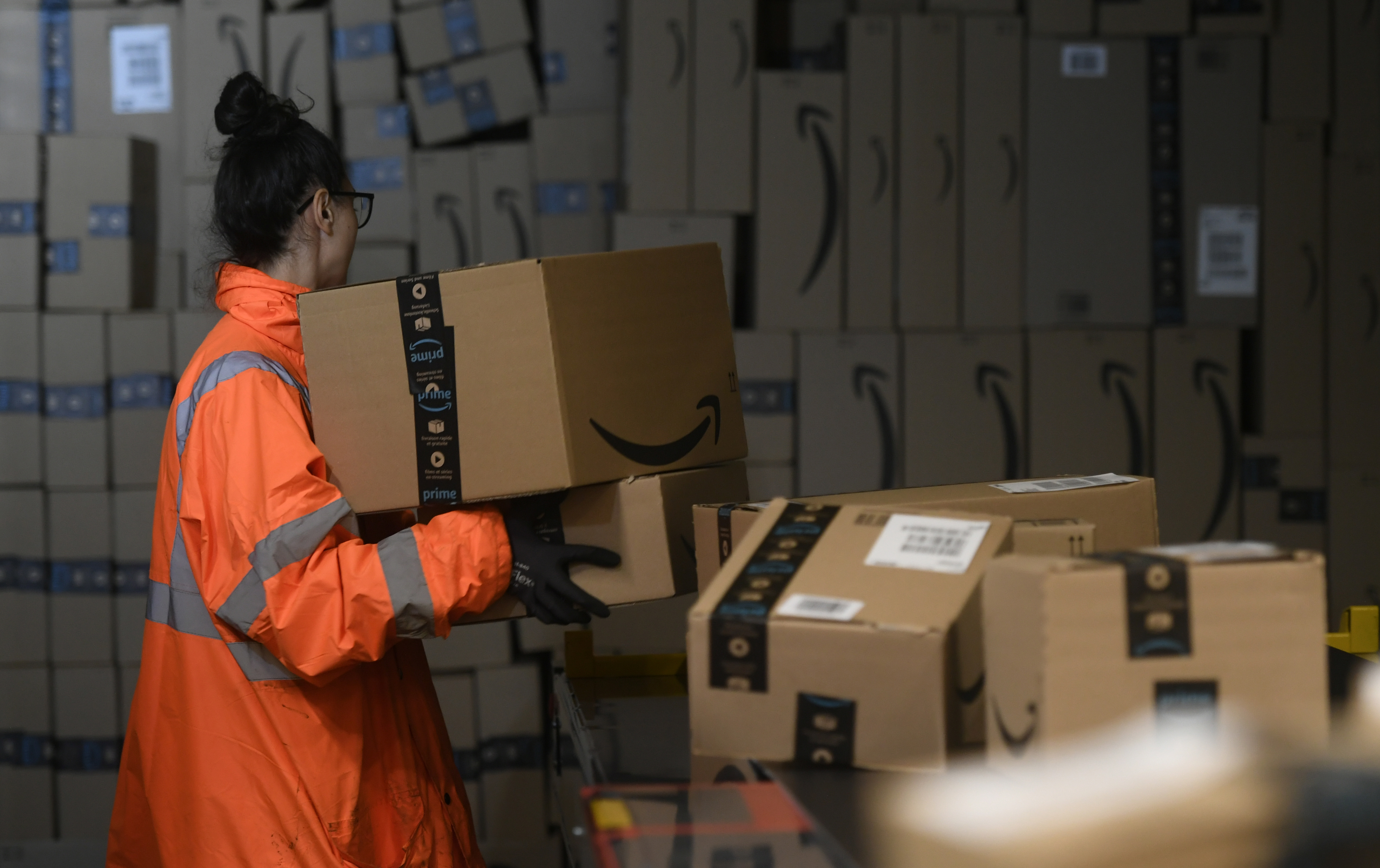 A warehouse employee handles an Amazon package at a distribution center.
