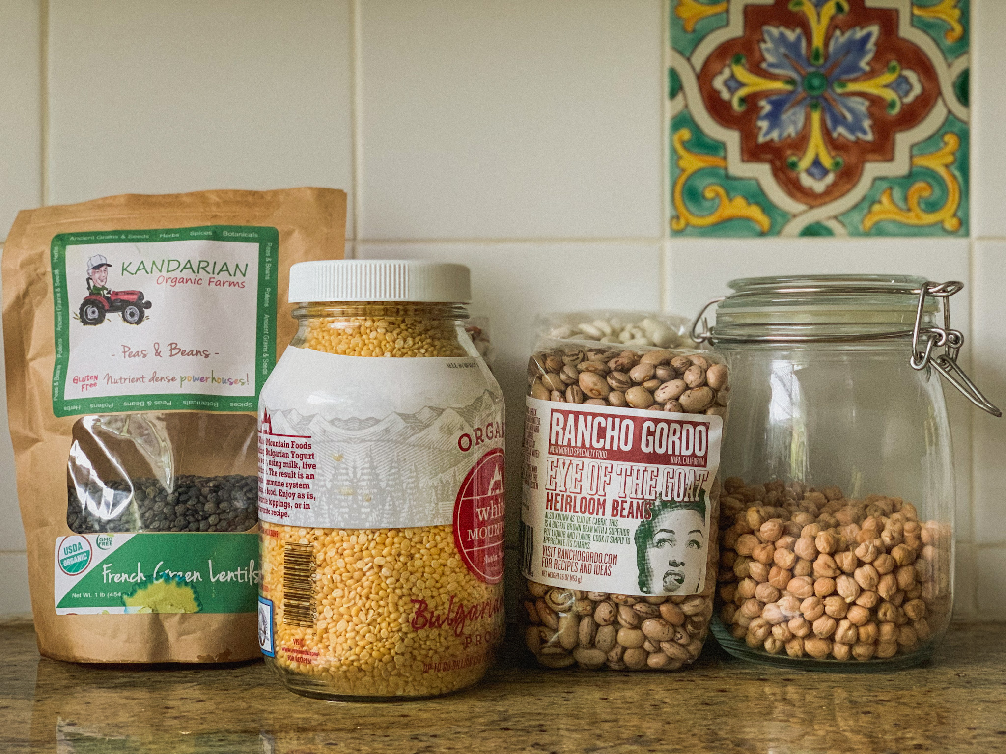 A row of dried beans in bags and jars are arrayed on a counter