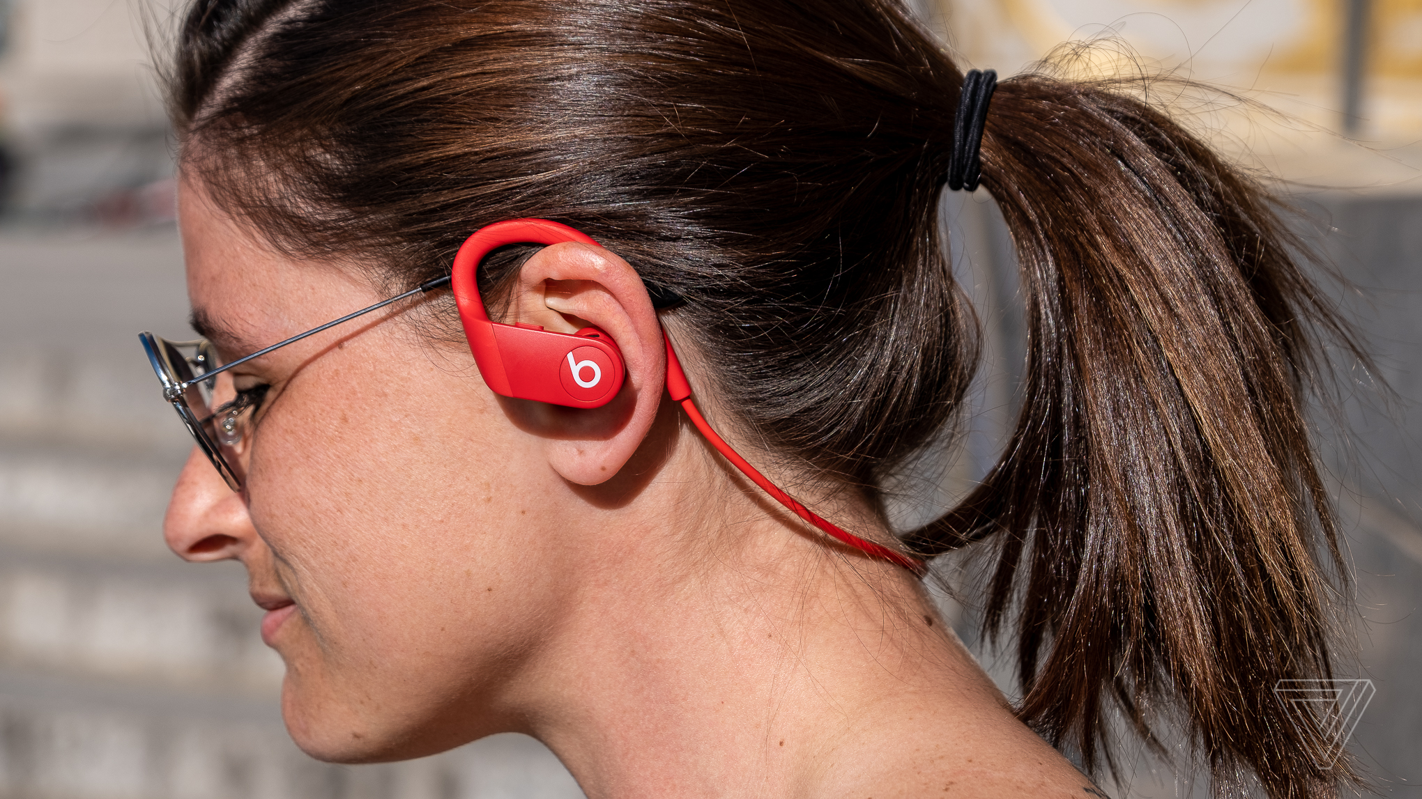 Powerbeats 4 earbuds seen from a side profile view.