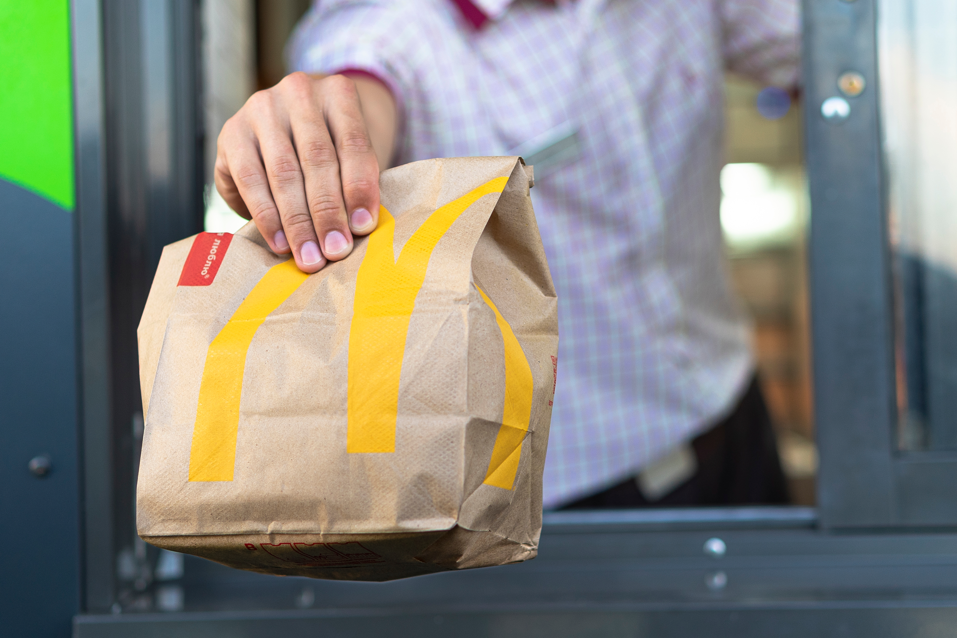 McDonalds worker holding bag of fast food at a drive-thru