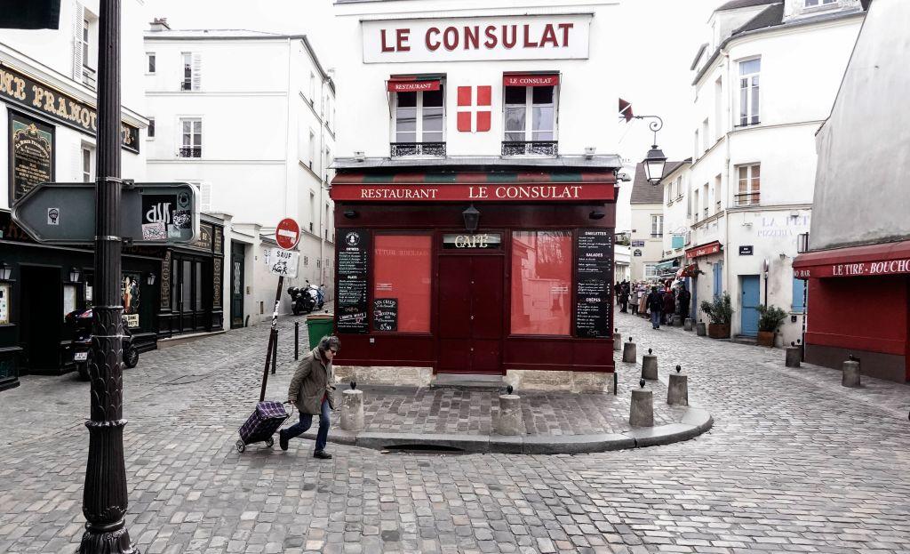 a woman walks past a closed restaurant in Paris