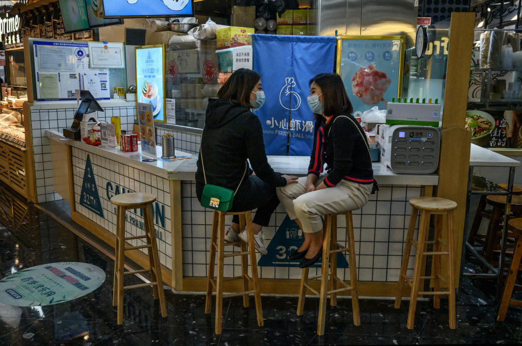 Two women sit on barstools wearing face masks at a small restaurant or bar