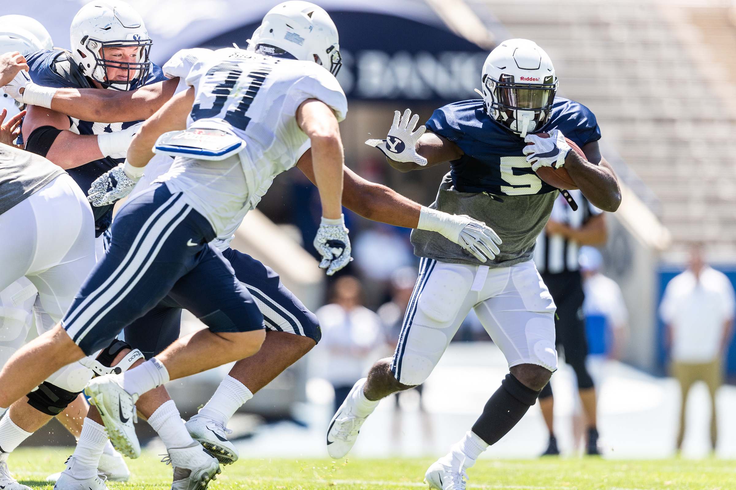 BYU running back Ty'Son Williams (5) runs with the ball as linebacker Max Tooley (31) defends during the Cougars' scrimmage at LaVell Edwards Stadium on Saturday, Aug. 10, 2019.