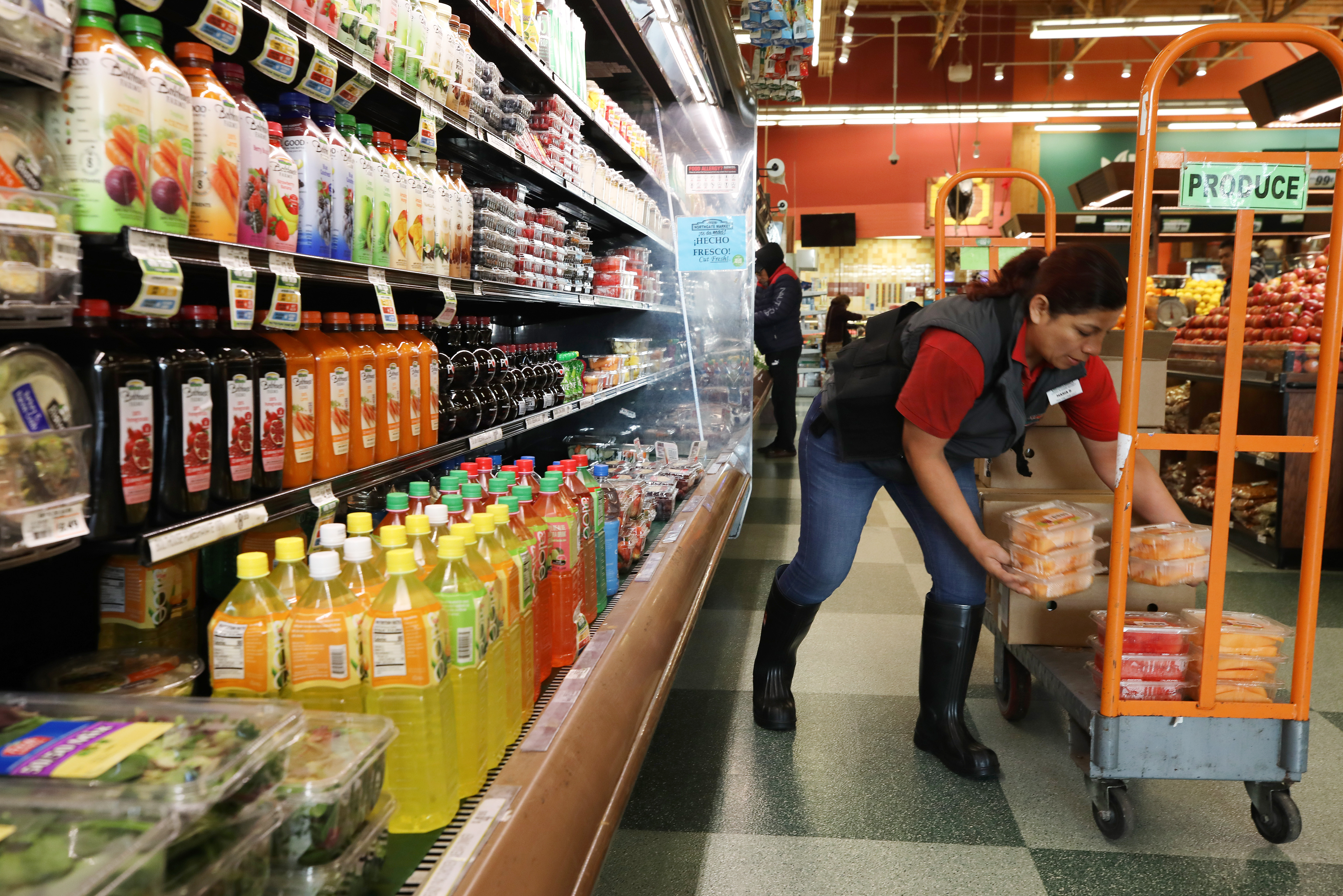 A woman stocks grocery store shelves
