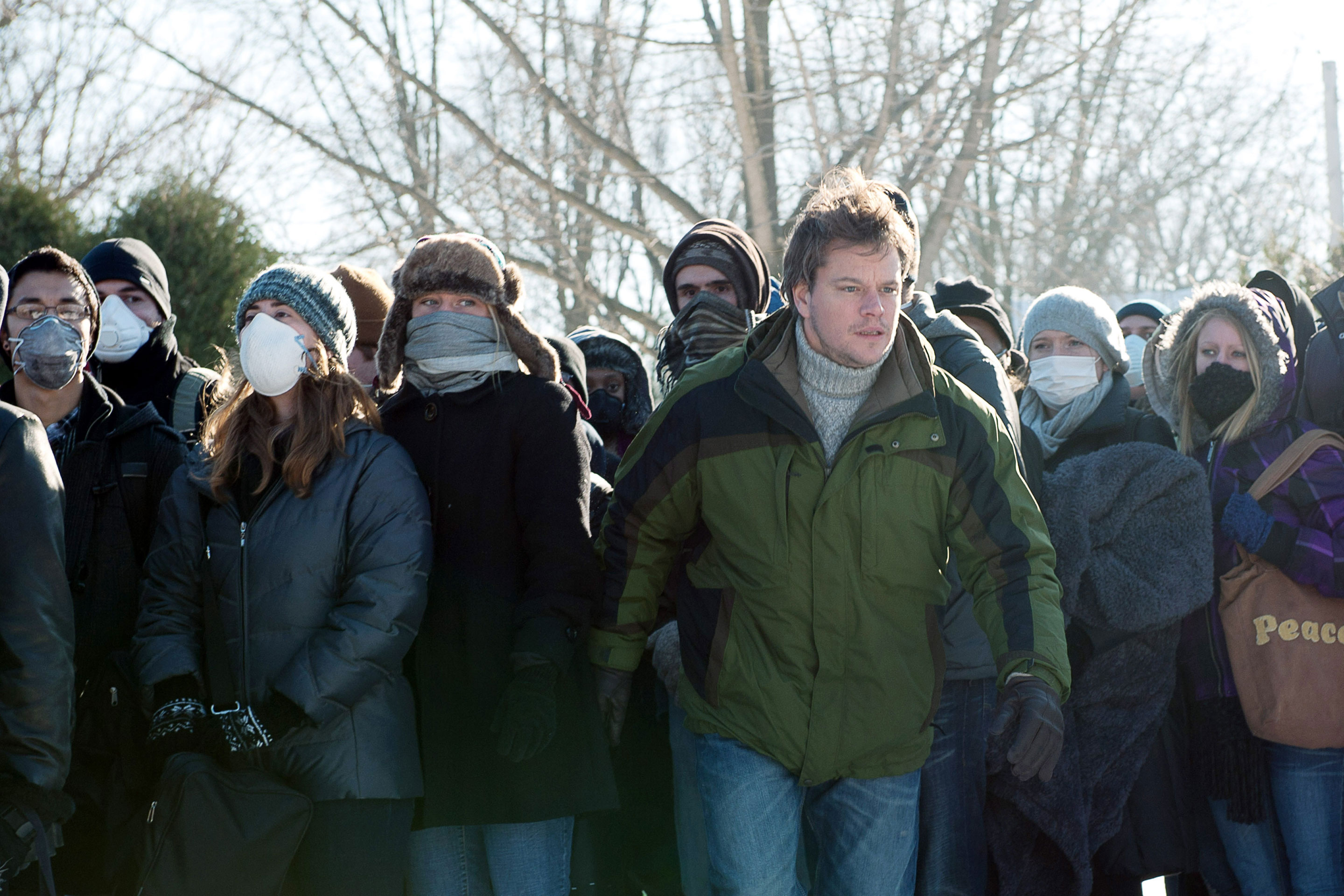 Matt Damon emerges from a crowd of people in coats and medical face masks in 2011's Contagion.