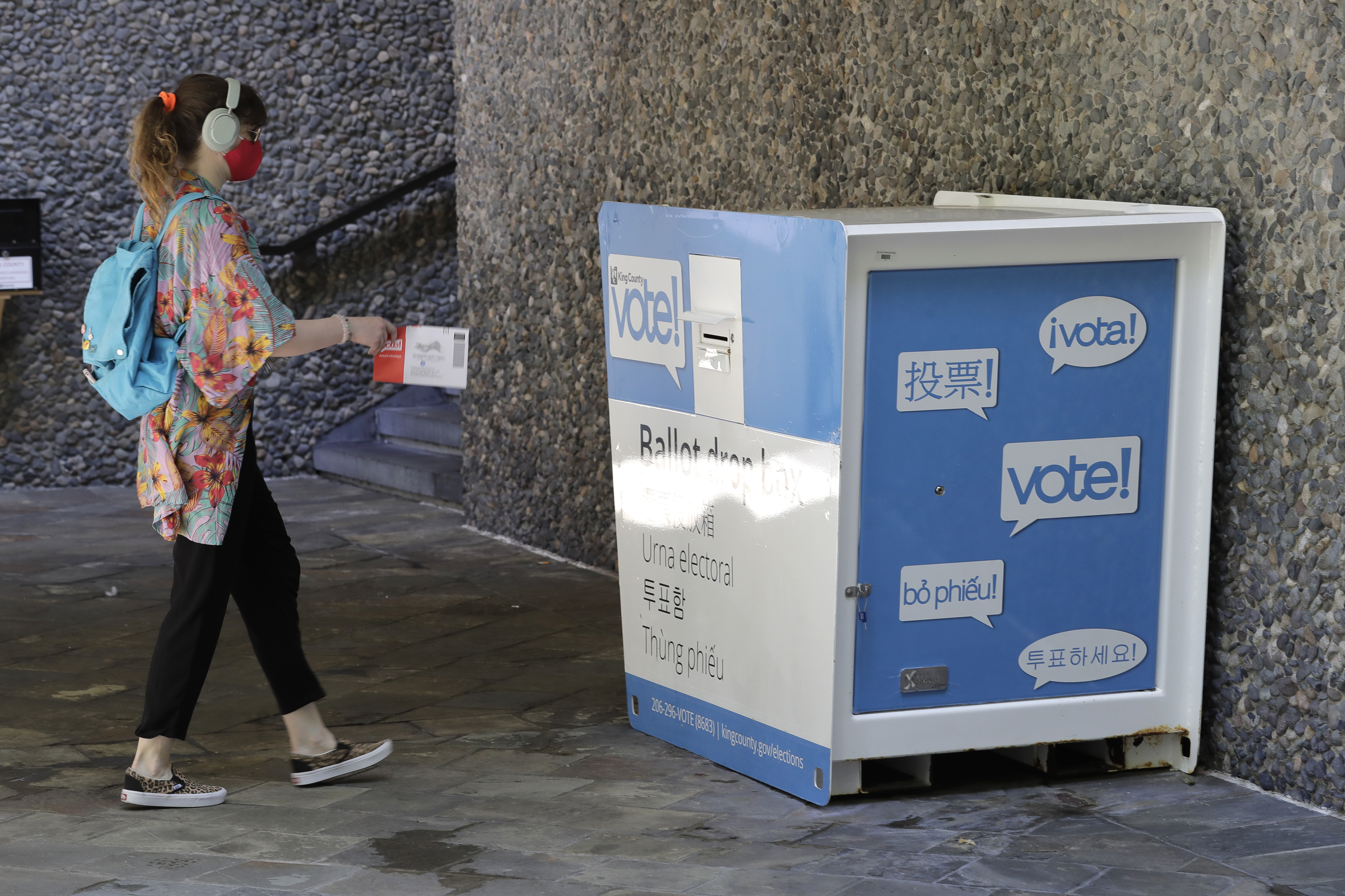 A person drops off a ballot for Washington state's primary election, Tuesday, Aug. 4, 2020, at a collection box at the King County Administration Building in Seattle.