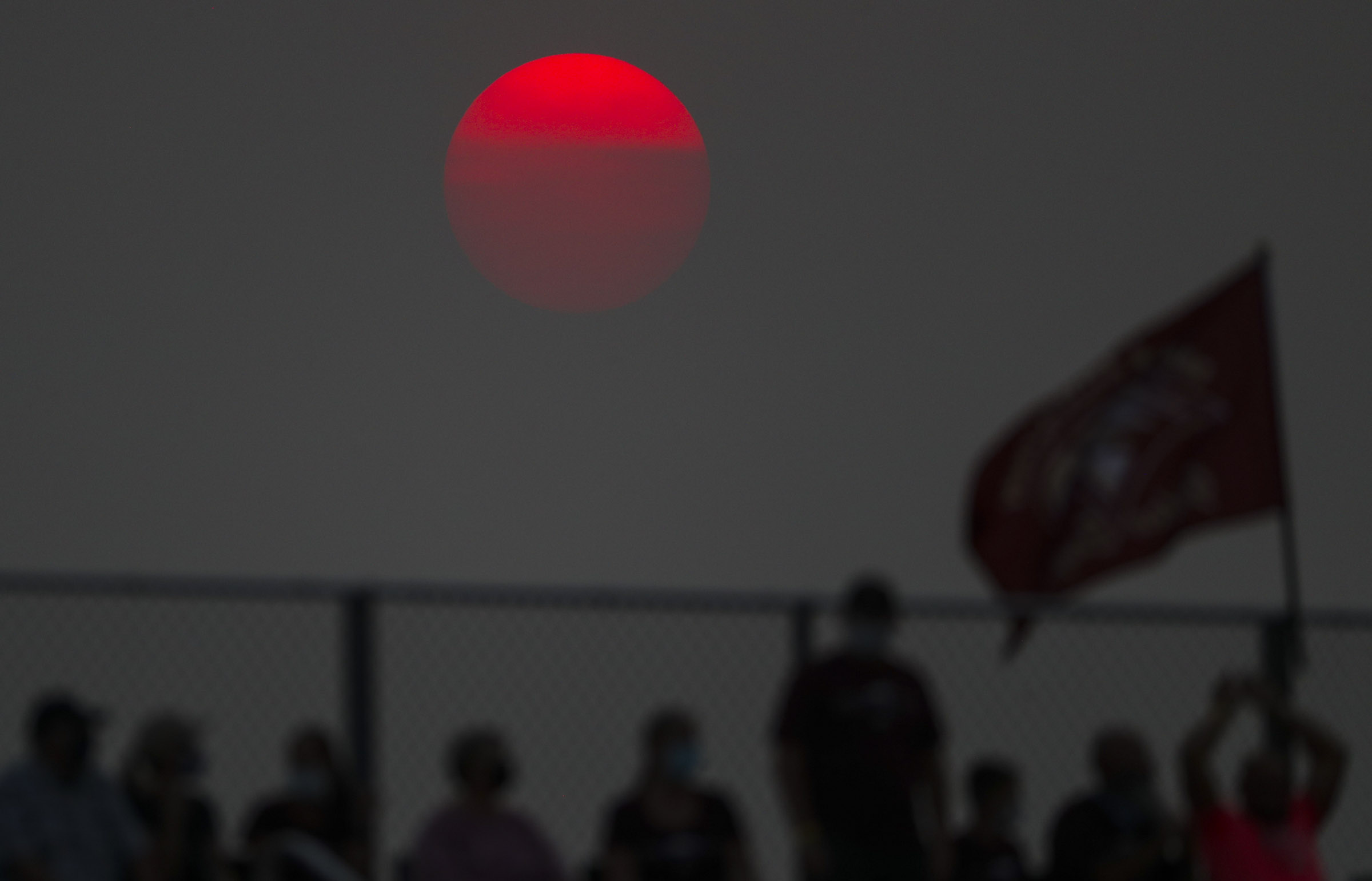 The sun glows orange as it sets over the Maple Mountain at Pleasant Grove football game in Pleasant Grove on Friday, Aug. 21, 2020.