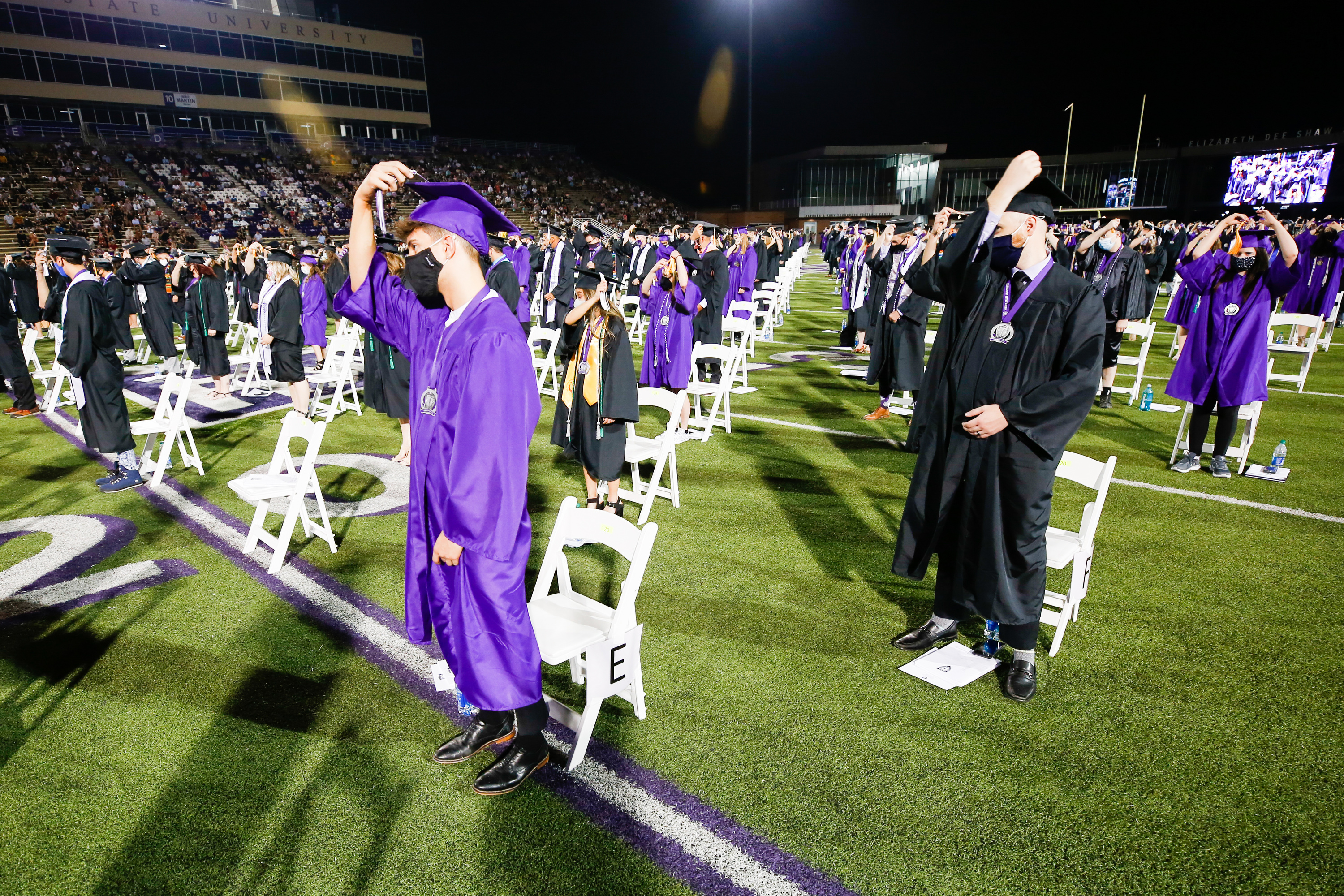 Students turn their tussles from right to left during the spring and summer graduation ceremonies at Stewart Stadium at Weber State University in Ogden on Saturday, Aug. 29, 2020.