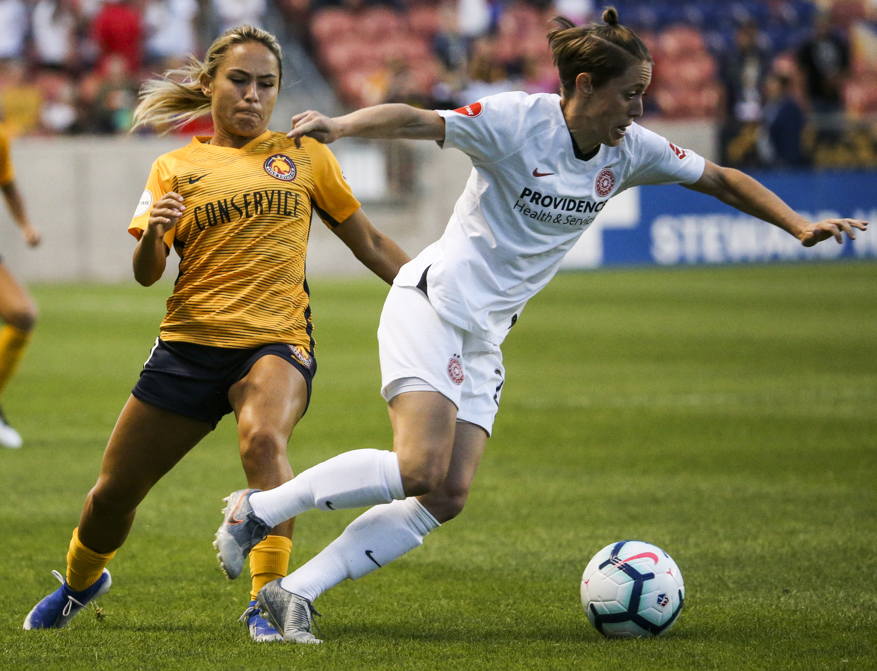 Portland Thorns FC defender Meghan Klingenberg (25) is tripped by Utah Royals FC midfielder Lo'eau LaBonta (9) during the first half of a National Womens Soccer League game at Rio Tinto Stadium in Sandy on Friday, Sept. 6, 2019.
