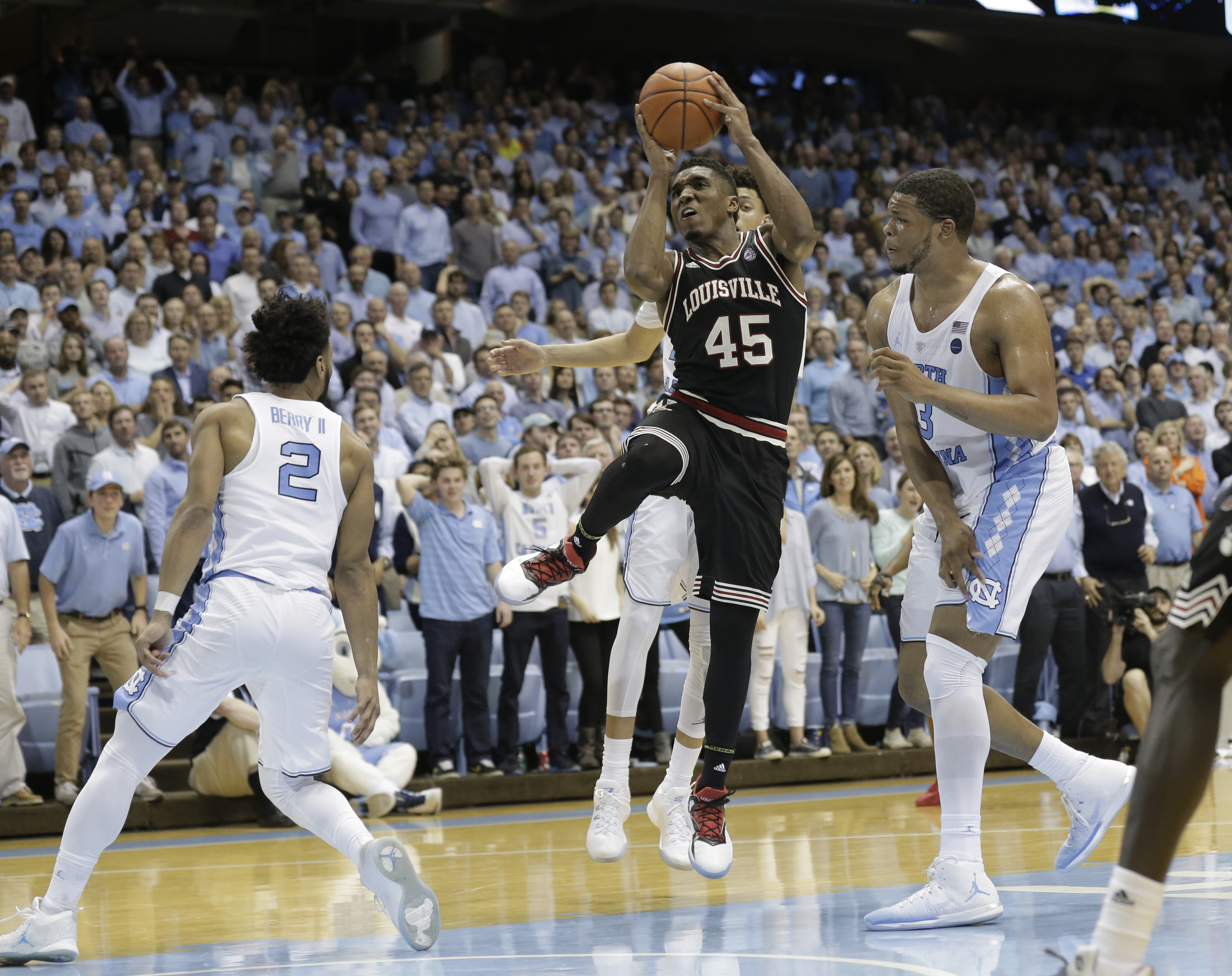 North Carolina's Joel Berry II (2) and Kennedy Meeks, right defend against Louisville's Donovan Mitchell (45) during the second half of an NCAA college basketball game in Chapel Hill, N.C., Wednesday, Feb. 22, 2017. North Carolina won 74-63. (AP Photo/Gerry Broome)