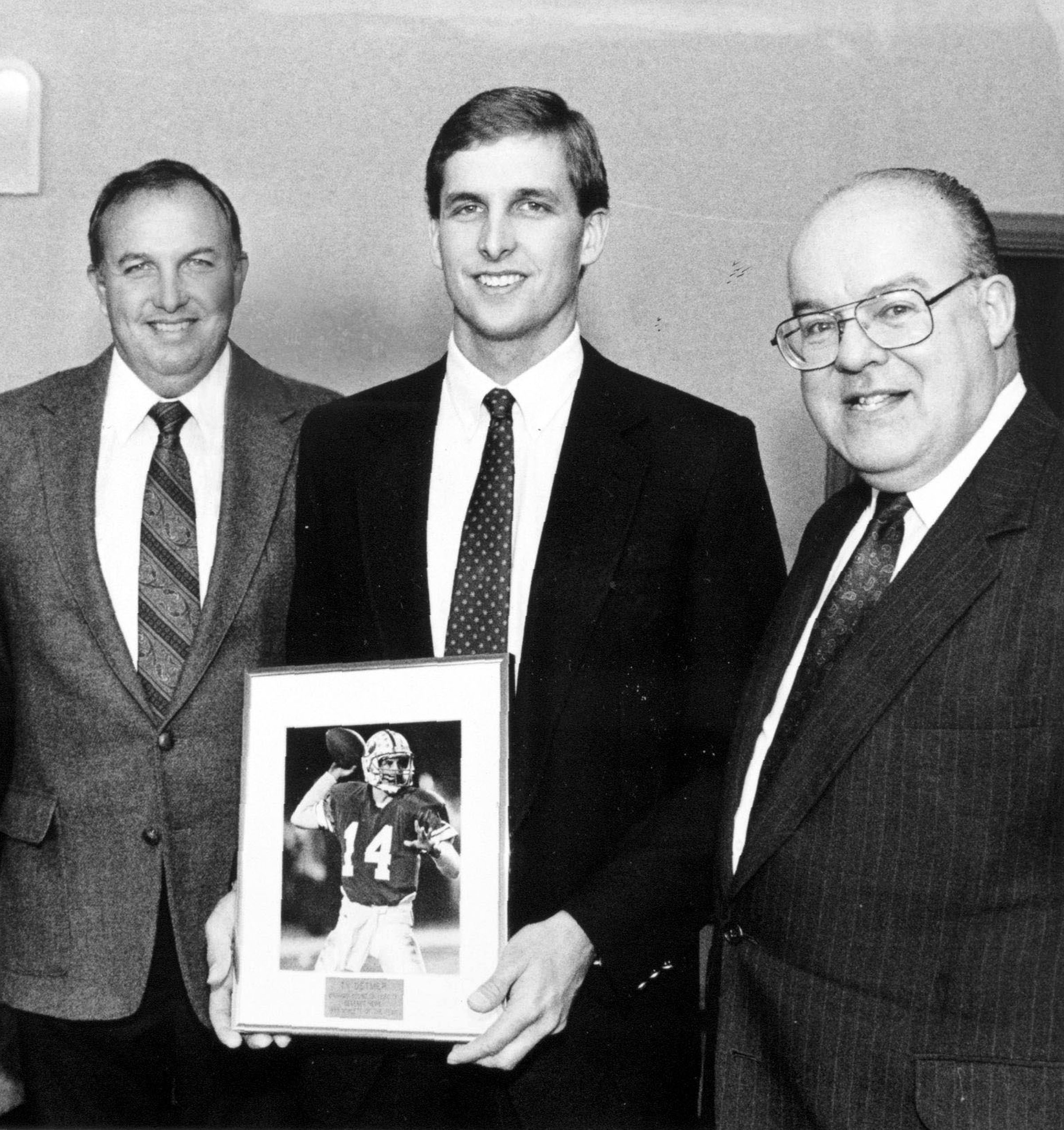 BYU Quarterbacks online photo gallery Ty Detmer, flanked by his father Sonny, left, plays the 1989 Deseret News' Athlete of the Year award he received from publisher William James Mortimer, right, during a luncheon in Detmer's honor in Provo. March 17, 1990. Sonny Detmer passed away Tuesday at the age of 76.