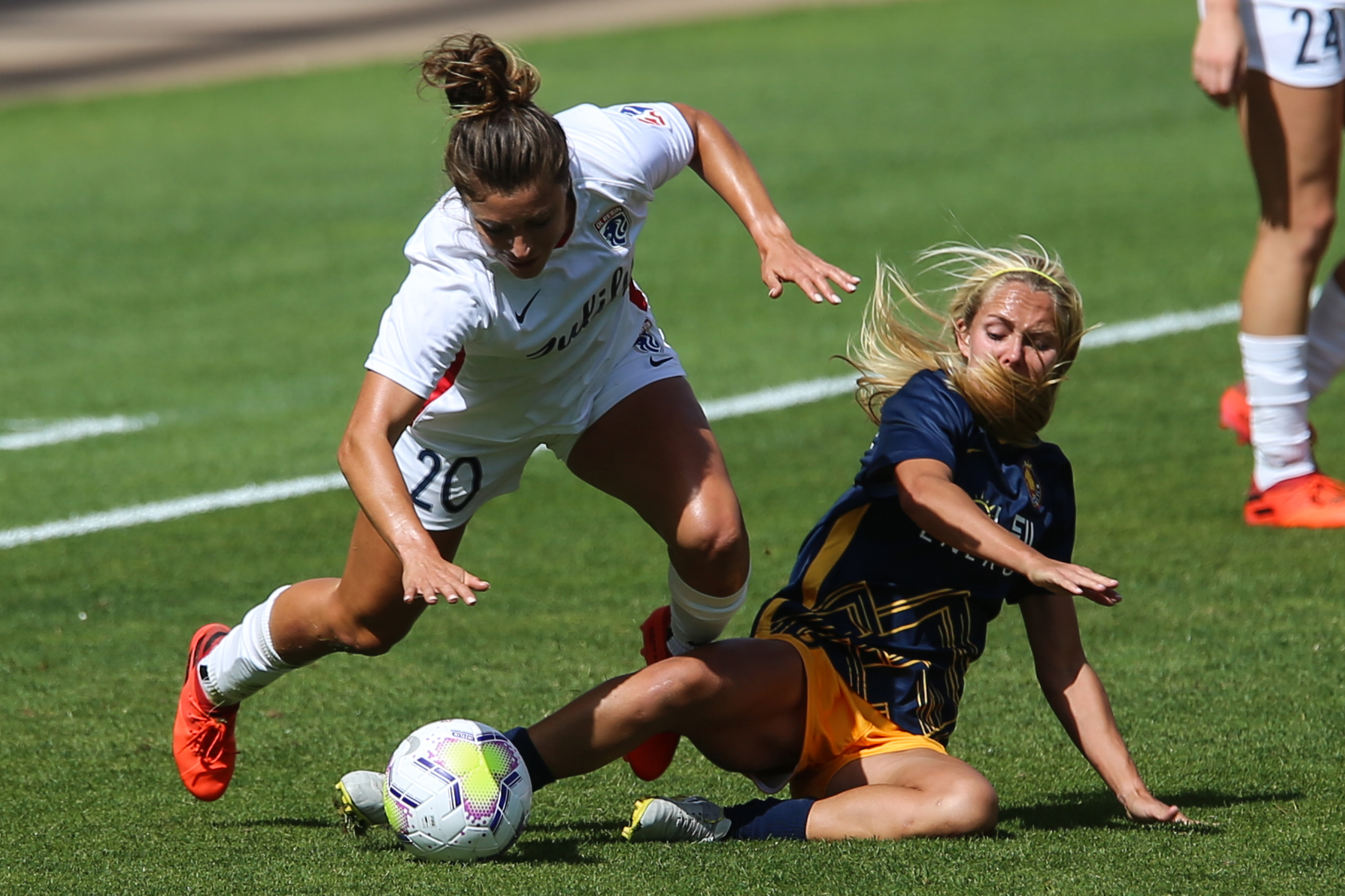 Utah Royals FC forward Brittany Ratcliffe (25) slide tackles the ball against OL Reign FC midfielder Rumi Utsugi (20) during a NWSL soccer game at Rio Tinto Stadium in Sandy on Saturday, Sept. 26, 2020.