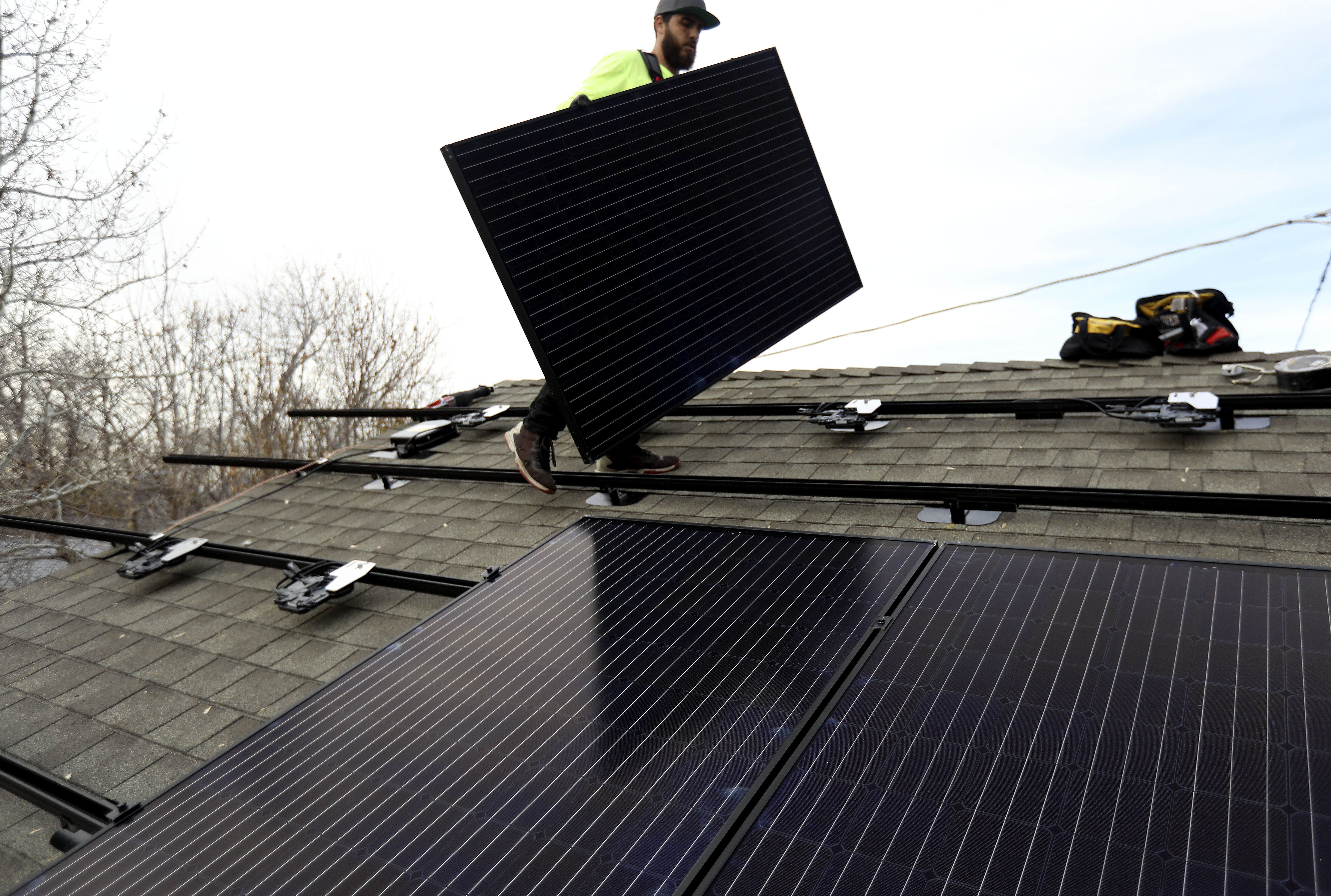 Dom Ontiveros, of Auric Energy, installs a solar panel on the 1,000th home that utilized the Empower SLC Solar program in Salt Lake City on Thursday, Nov. 14, 2019. Empower SLC Solar, a community-led program in Salt Lake County, helps residents overcome the logistical and financial hurdles of going solar.