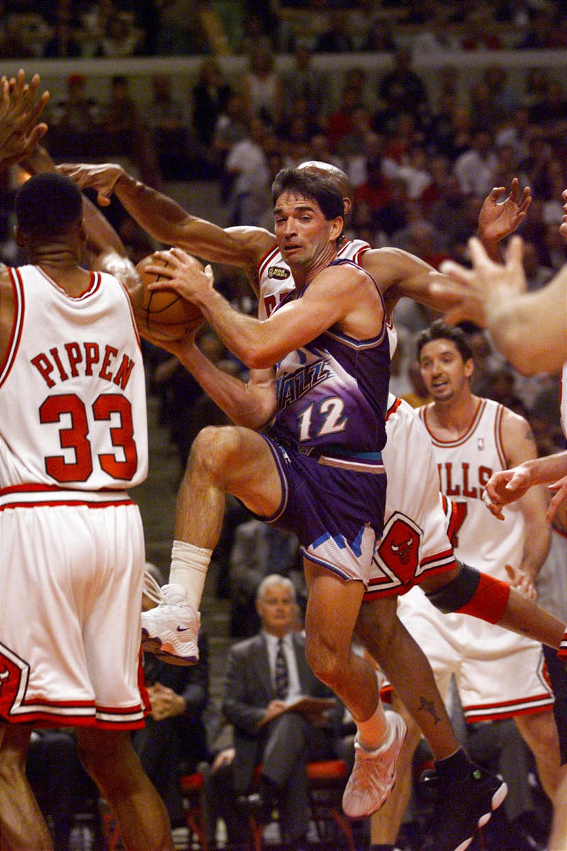 Jazz guard John Stockton (12) slices past Scottie Pippen (33) and the Bulls' defense during the 1998 NBA Finals.