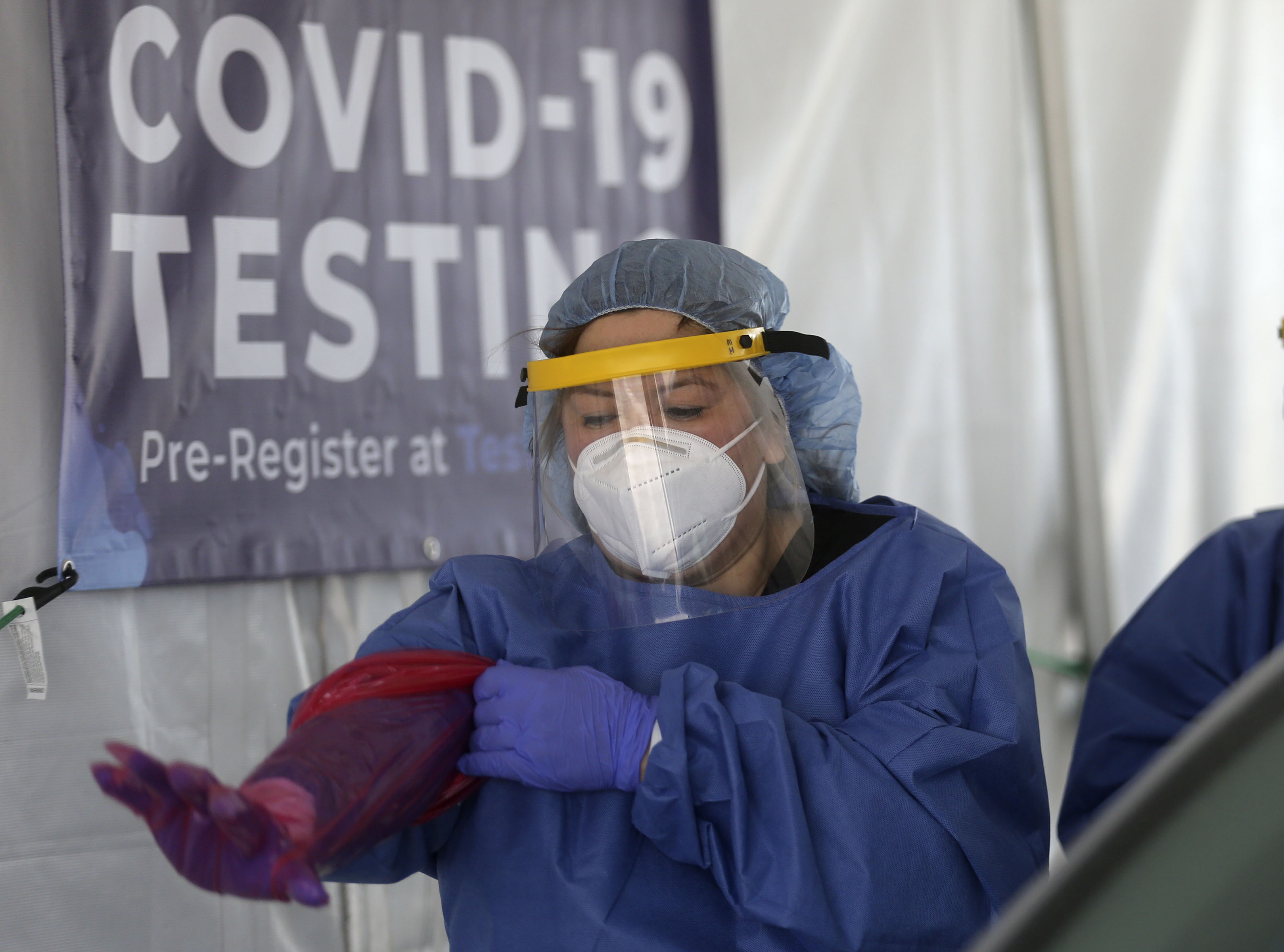 Eve Kovacs, infection control nurse, puts on a fresh glove before administering a COVID-19 test at a TestUtah free testing site outside of the Kearns Recreation Center at Oquirrh Park in Kearns on Wednesday, July 8, 2020.
