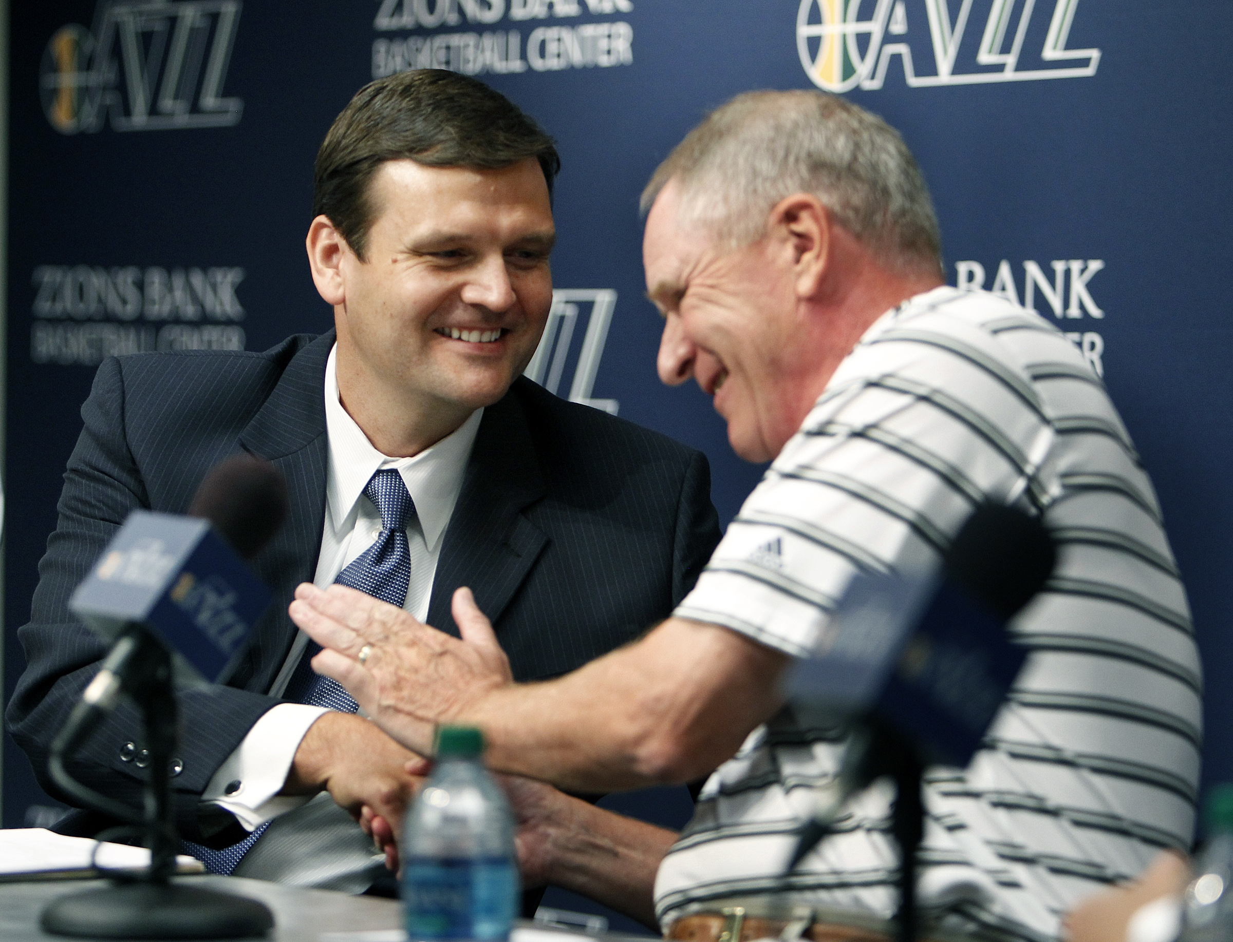 Kevin O'Connor, right, Executive Vice President of Basketball Operations for the Utah Jazz, shakes hands with Dennis Lindsey as Lindsey is introduced as the team's general manager at the Zions Bank Basketball Center in Salt Lake City, Tuesday, Aug. 7, 2012.