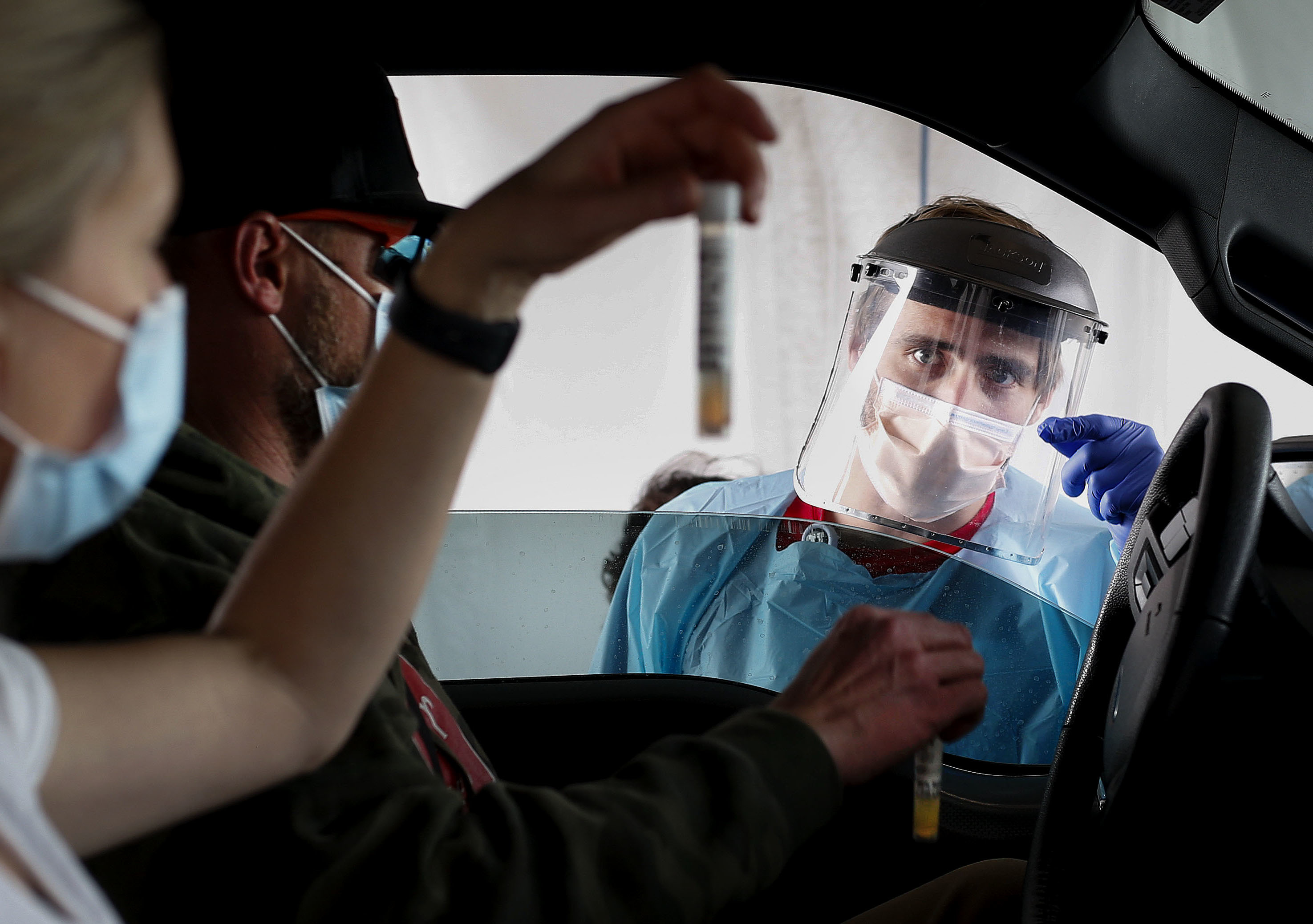 Liz and Sam Rodgers verify their COVID-19 saliva tests to Josh Anderson at a drive-thru test site at University of Utah Health's South Jordan Health Center in South Jordan on Friday, Oct. 2, 2020.