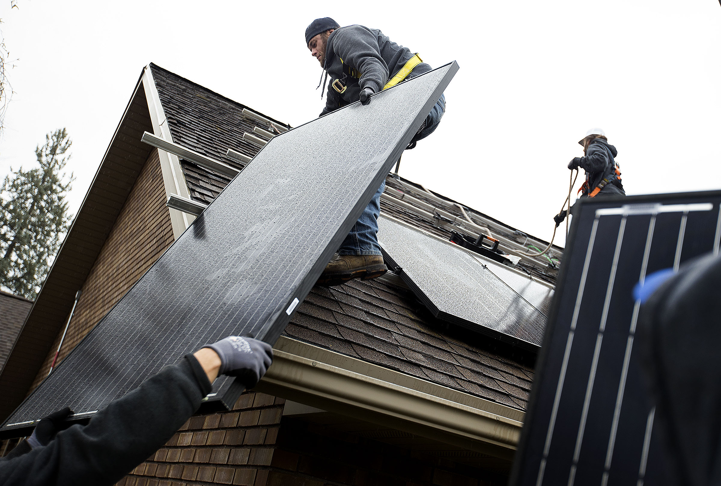 Justin Kourbelas and Tyler Eichmeier, of Go Solar Energy, install solar panels on a house in Holladay on Friday, April 6, 2018.