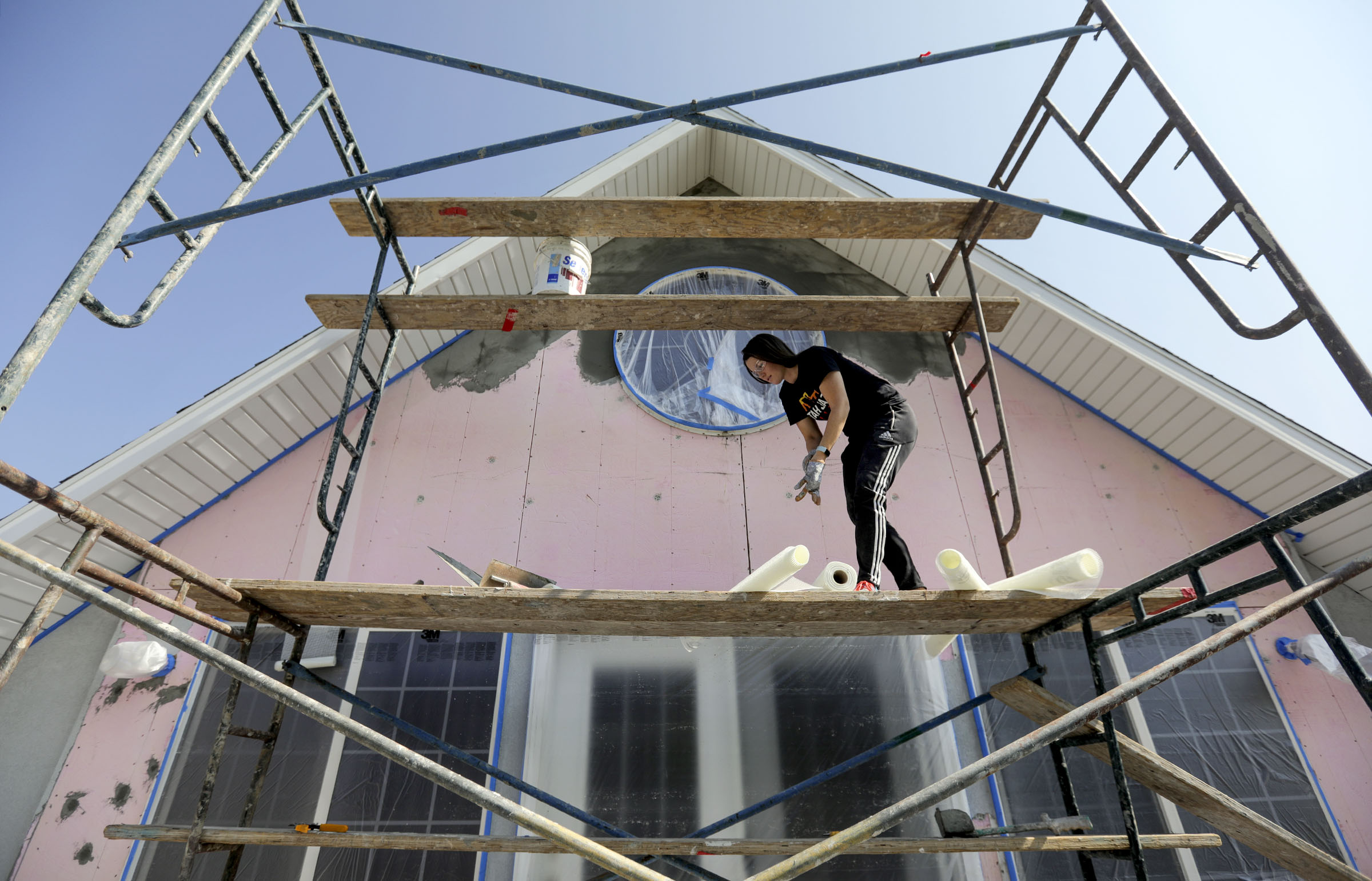 Kelsie Wadsworth preps a wall for stucco as she works on a house with McCoy's Stucco Repair in Springville on Tuesday, Oct. 6, 2020. Wadsworth was connected to McCoy's Stucco Repair through the Bacon app.
