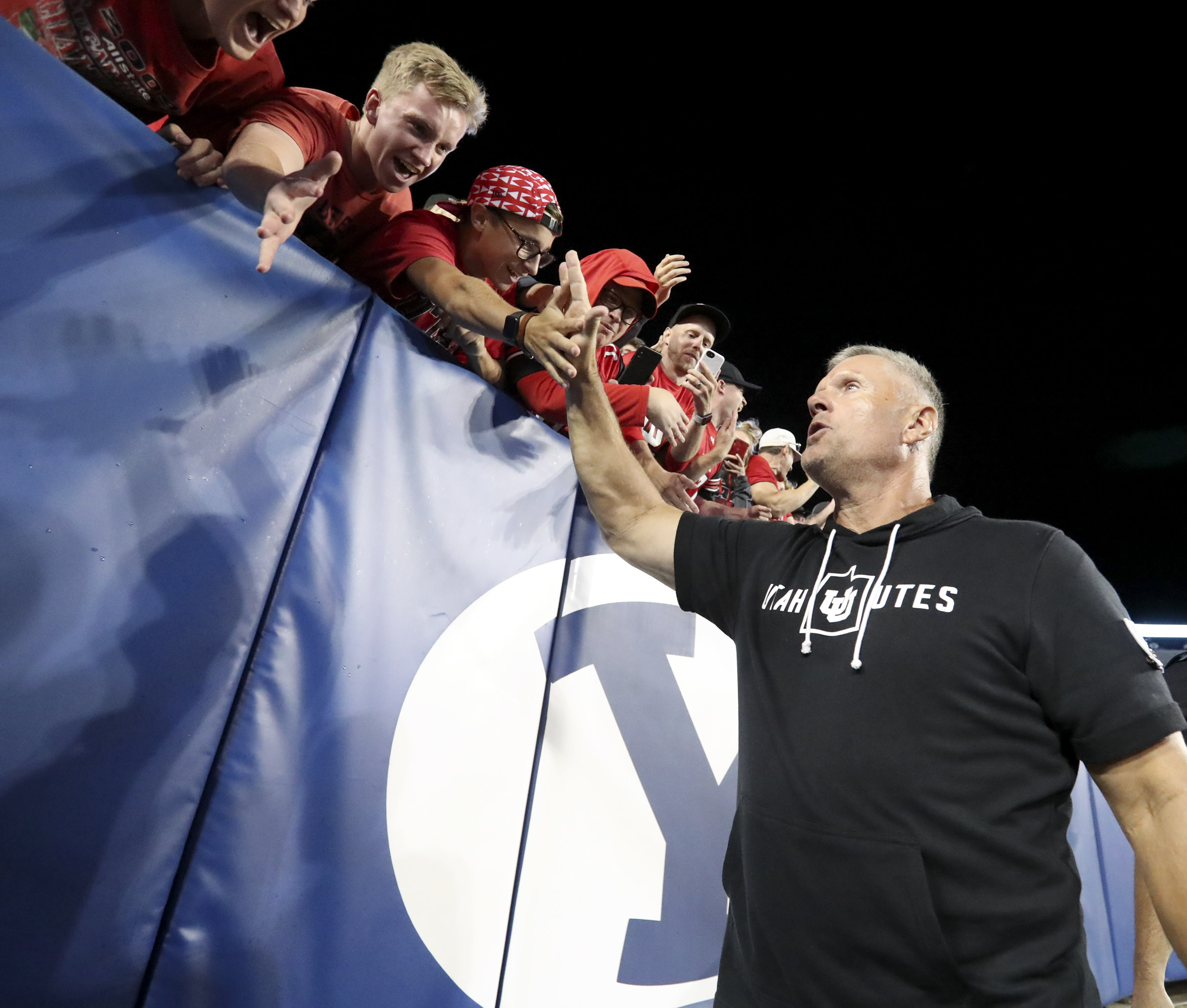 Fans stretch to high-five Utah Utes head coach Kyle Whittingham after the Utes defeated BYU 30-12 at LaVell Edwards Stadium in Provo on Friday, Aug. 30, 2019.
