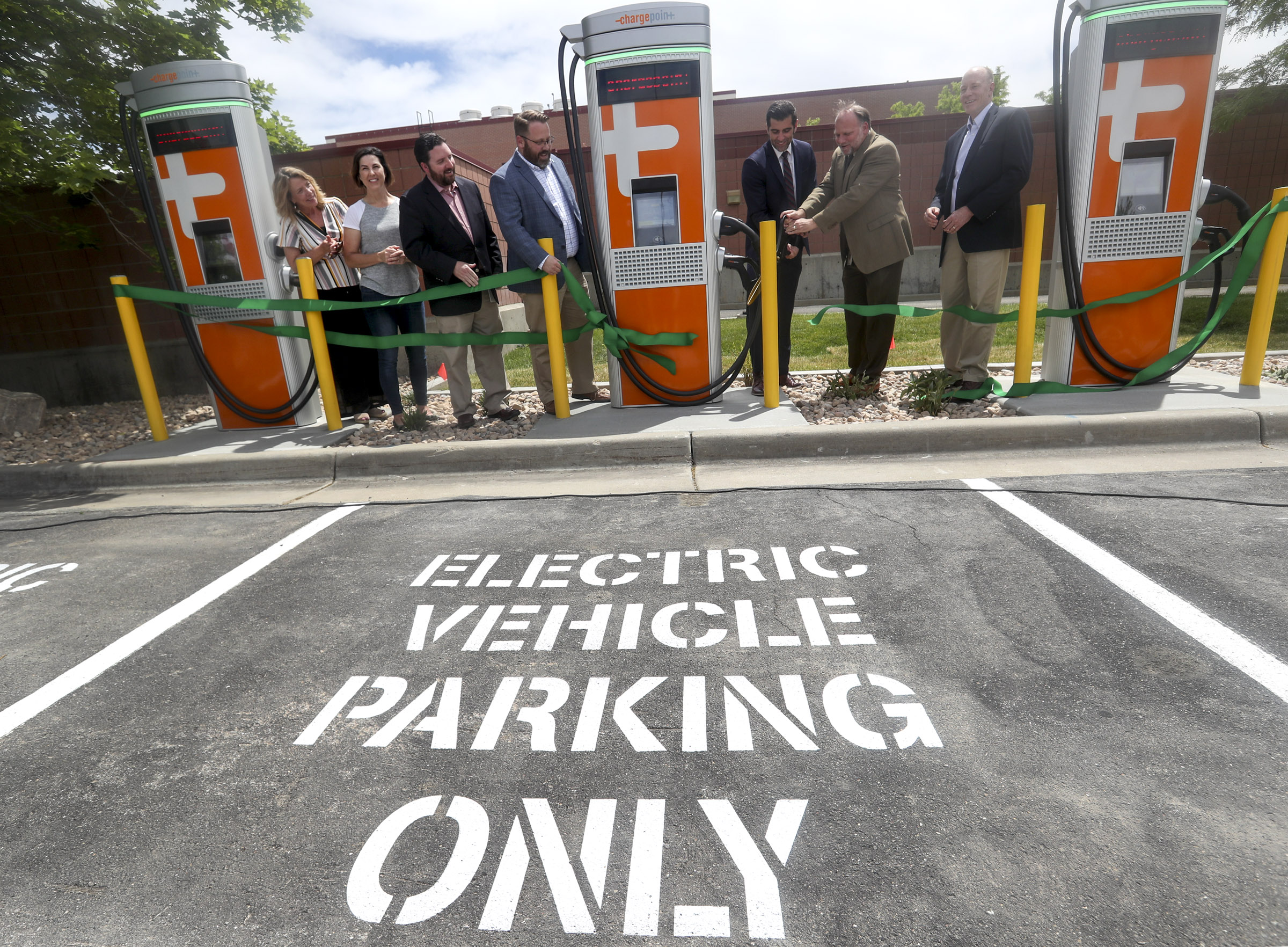 Sandy Major Kurt Bradburn is joined by Rocky Mountain Power's James Campbell and other dignitaries during a ribbon-cutting ceremony at Sandy City Hall on Wednesday, June 12, 2019. During the ceremony, officials announced the availability of 45 electric charging vehicle stations at city facilities.