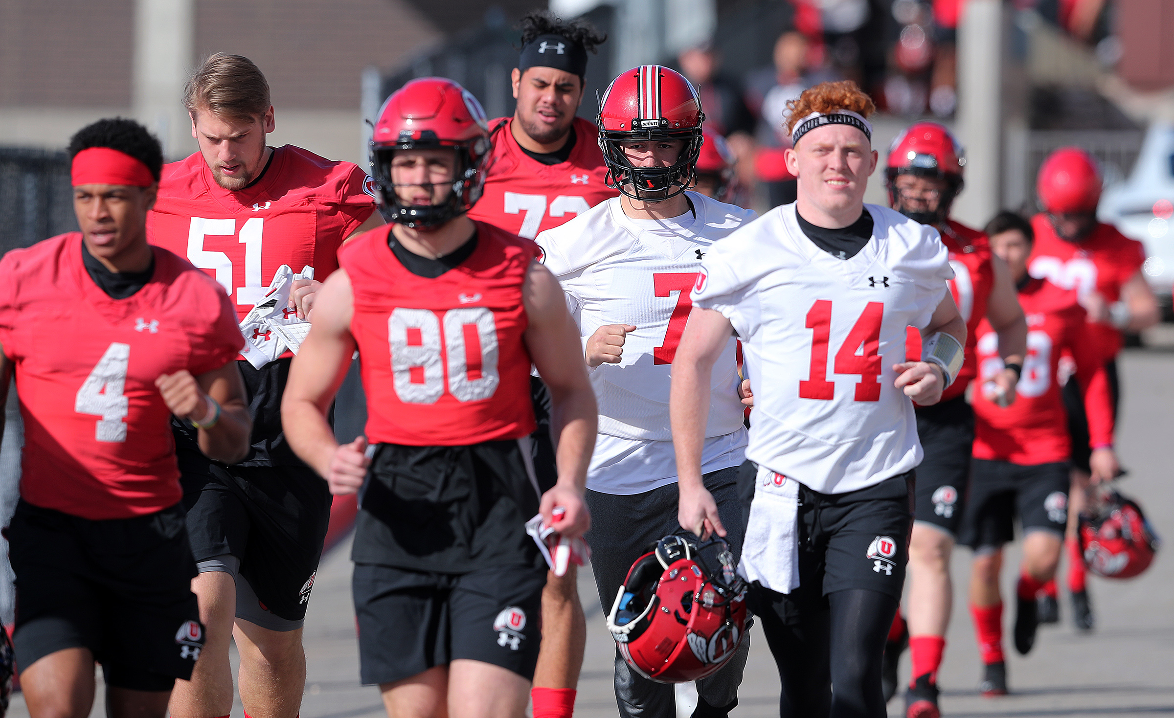 Members of the University of Utah football team run out to the practice fields as they open spring camp in Salt Lake City on Monday, March 2, 2020.