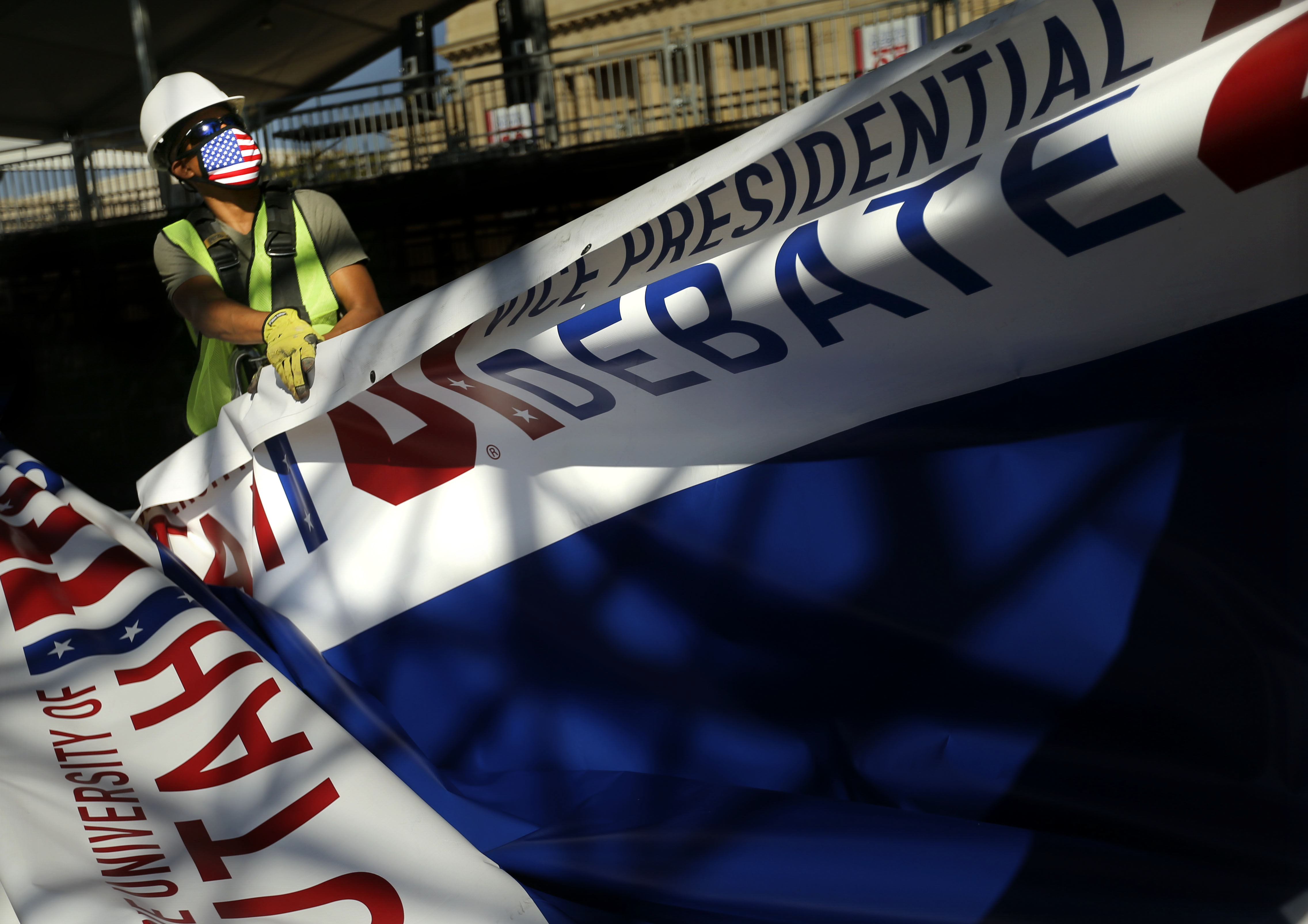 Piero Mucha, a member Local 99 of the International Alliance of Theatrical Stage Employees, removes signage at the University of Utah in Salt Lake City on Thursday, Oct. 8, 2020, the day after the vice presidential debate.