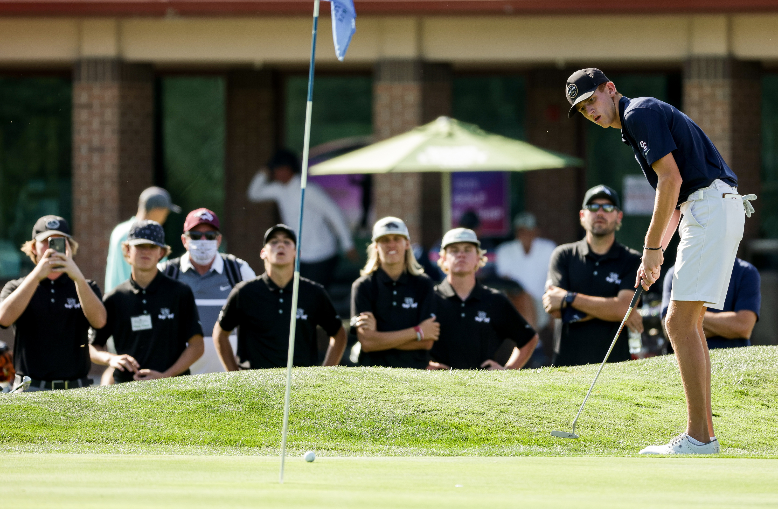 With teammates looking on, Luke Schone, of Crimson Cliffs, putts on the 18th green during the final round of the 4A boys golf tournament at Meadow Brook Golf Course in Taylorsville on Thursday, Oct. 8, 2020.