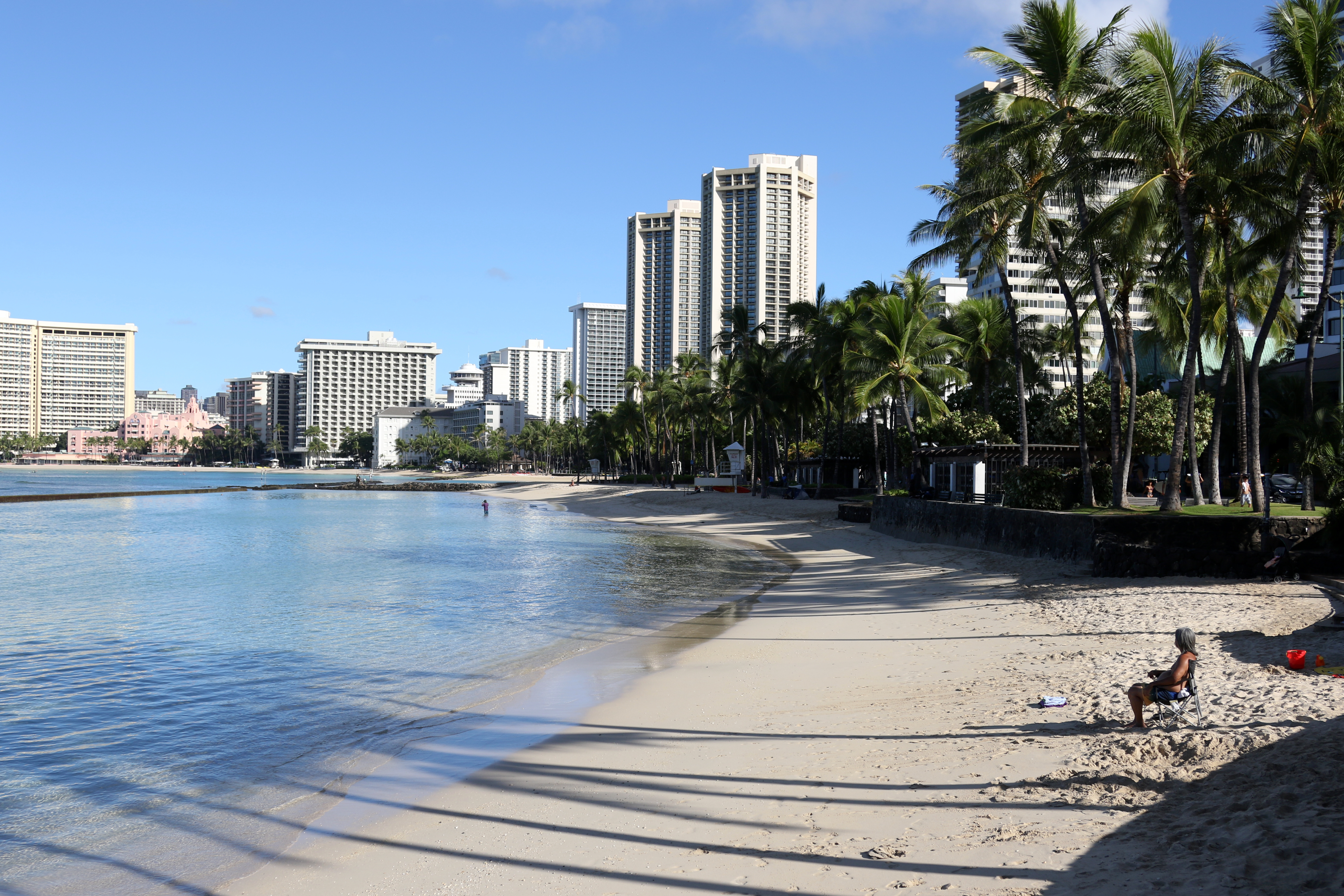 A man sits on a nearly empty Waikiki Beach in Honolulu, Friday, Oct. 2, 2020. After a summer marked by a surge of coronavirus cases in Hawaii, officials plan to reboot the tourism based economy later this month despite concerns about the state's pre-travel testing program.