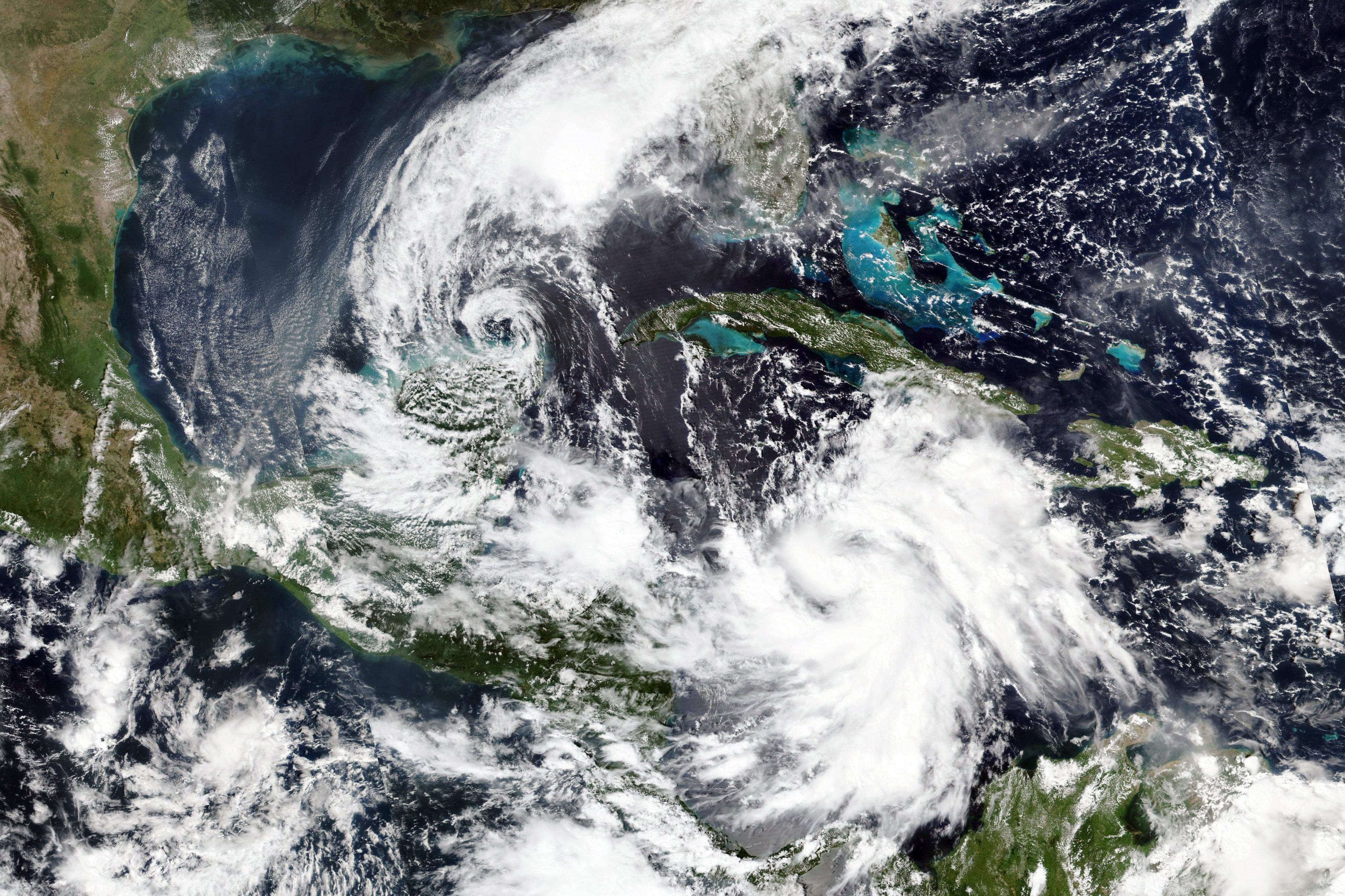This Monday, Oct. 5, 2020, satellite image released by NASA Worldview, Earth Observing System Data and Information System (EOSDIS) shows Tropical Storm Gamma, left, which soaked part of Mexico over the weekend and a strengthening Hurricane Delta, lower right, which is on a course to pass by the Cayman Islands early Tuesday.