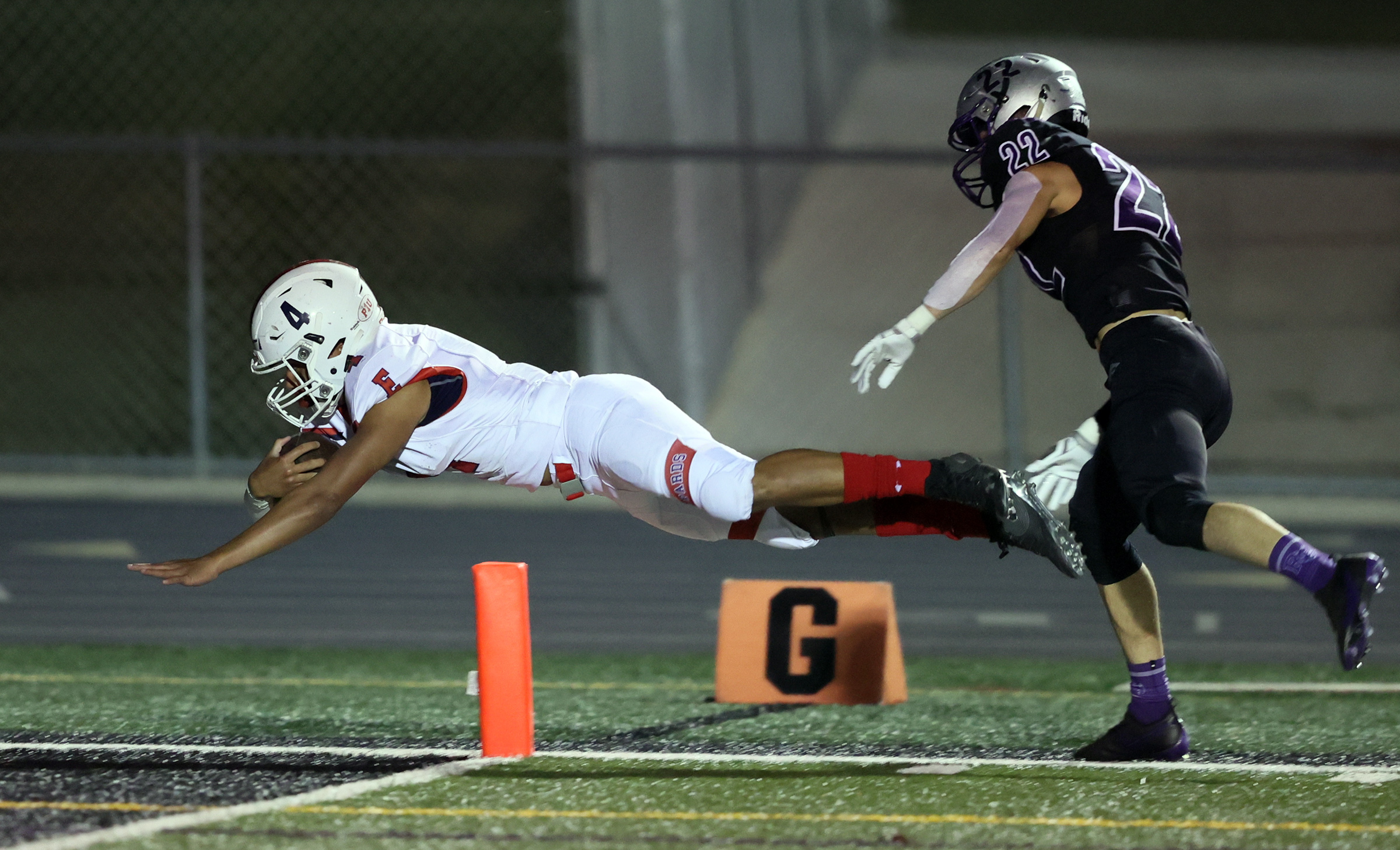 East's Siona Vailahi dives into the end zone for a score with Riverton's Colin Hauge chasing from behind as East and Riverton play a high school football game in Riverton on Friday, Oct. 9, 2020. East won 36-20.