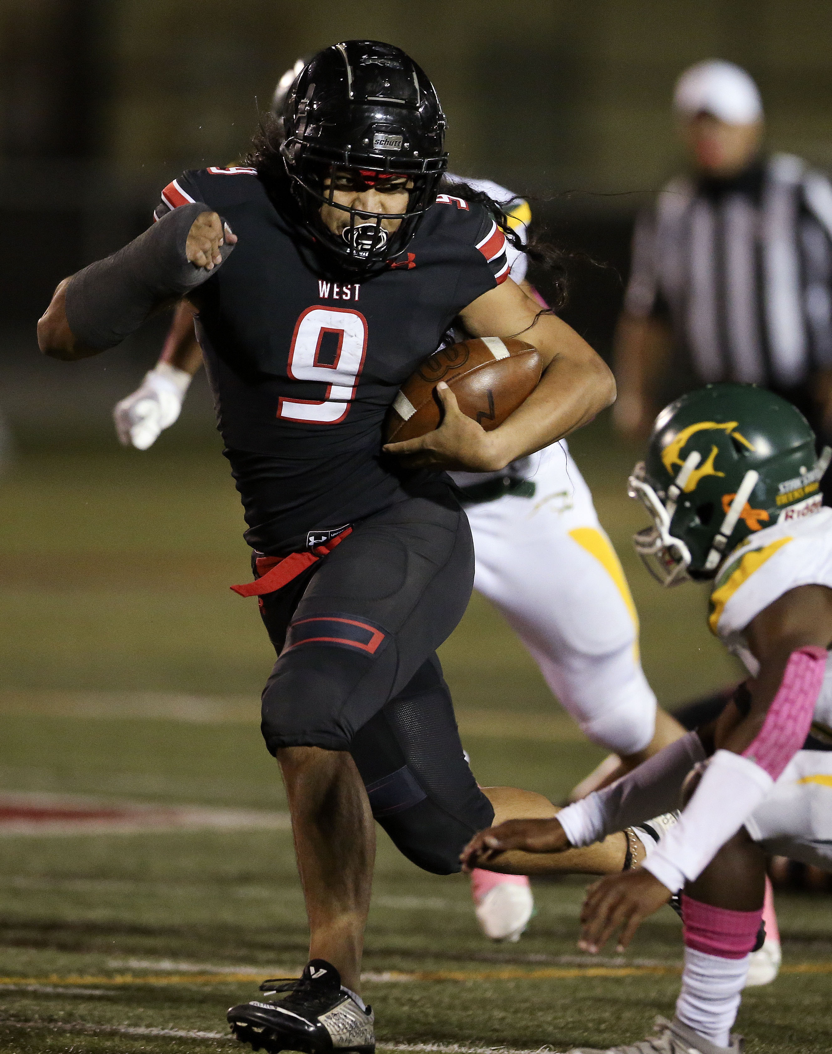 West High's Johnny Alo (9) gains yardage in the game against Kearns at West High School in Salt Lake City on Friday, Oct. 9, 2020.