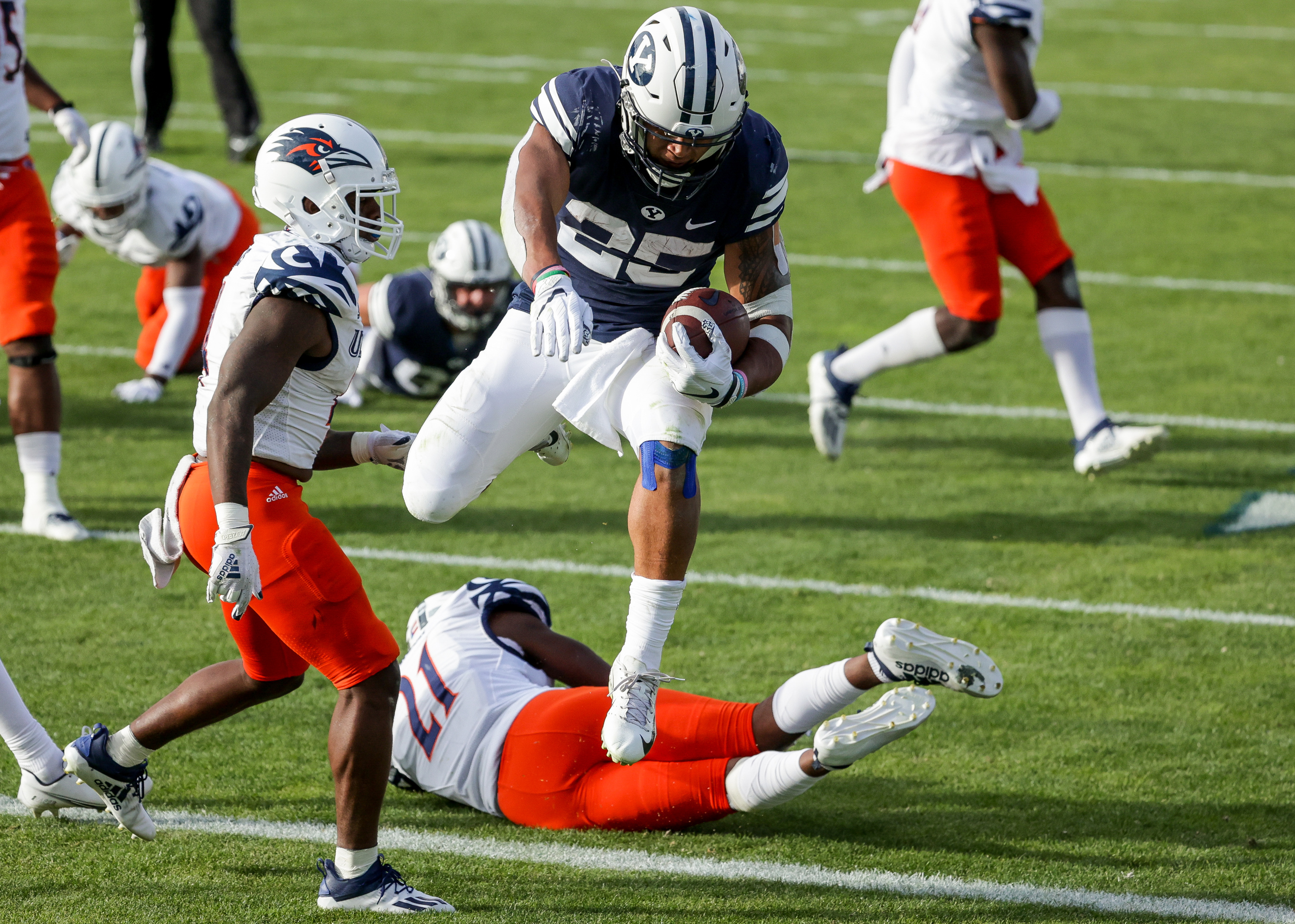 Brigham Young Cougars running back Tyler Allgeier (25) runs into the end zone over UTSA Roadrunners cornerback Ken Robinson (21), giving the Cougars a 27-13 lead after the PAT missed, at LaVell Edwards Stadium in Provo on Saturday, Oct. 10, 2020.