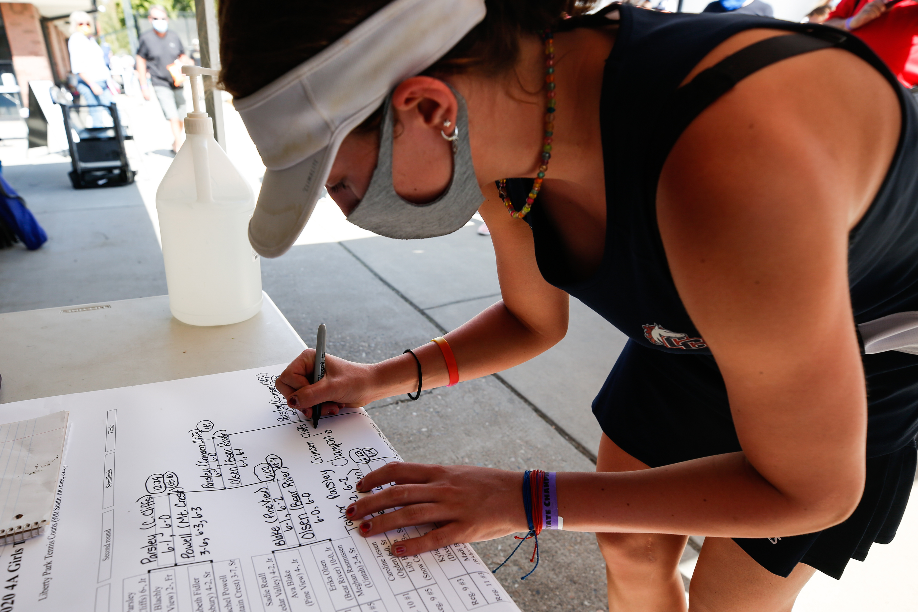 Taylor Parsley of Crimson Cliffs writes her name on the bracket sheet after winning the UHSAA 4A state championship first singles final at Liberty Park in Salt Lake City on Saturday, Oct. 10, 2020.