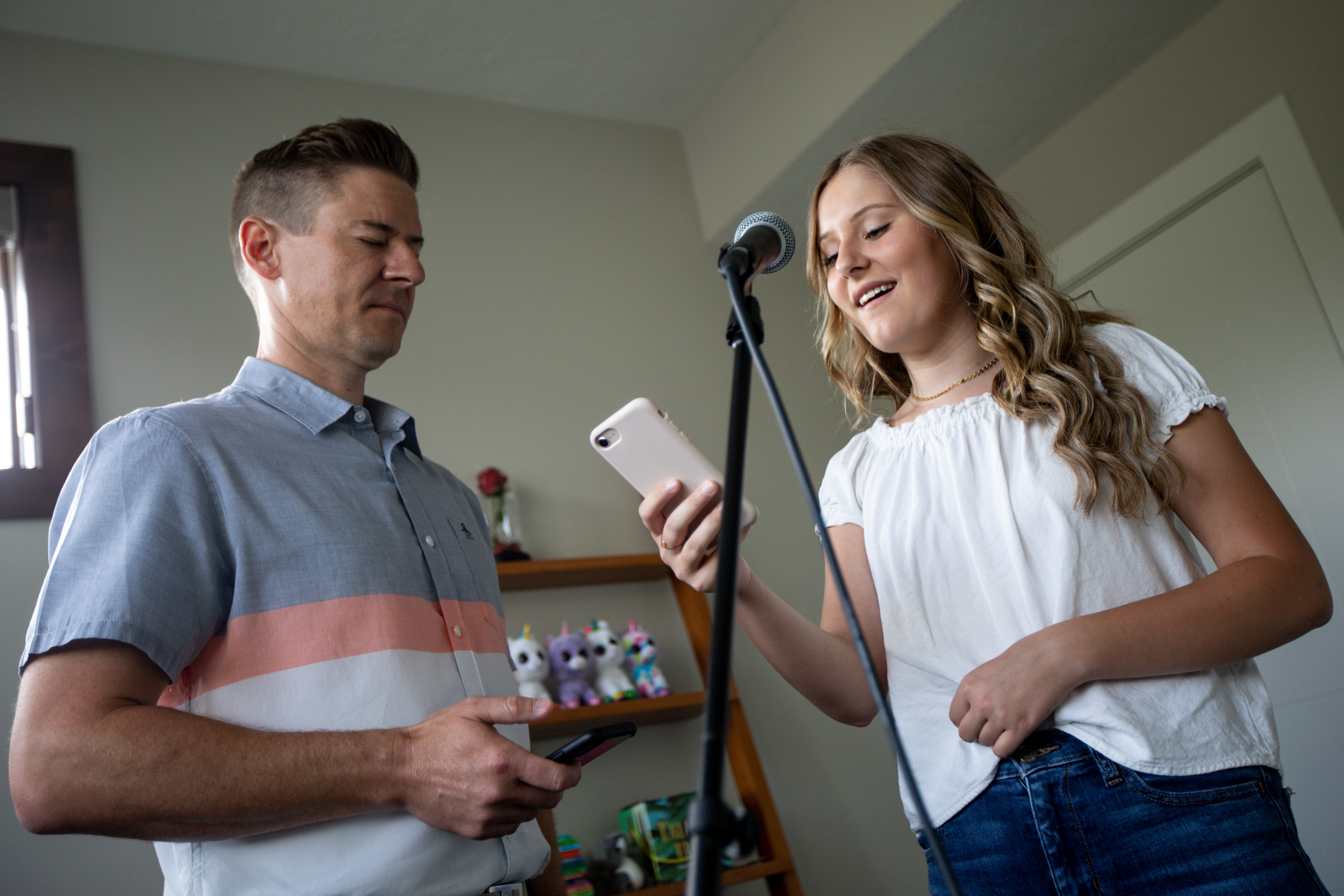 "Mat and Savanna Shaw practice a cover of the song ""Shallow"" in their family home's loft while the iPad they use to record their duets charges on Thursday, May 14, 2020. The father-daughter duets went viral on YouTube as they shared their passion for music amid the COVID-19 pandemic. ""The one thing more contagious than a virus is hope and so we're just doing our small part in the world to spread some hope,"" Mat Shaw said."
