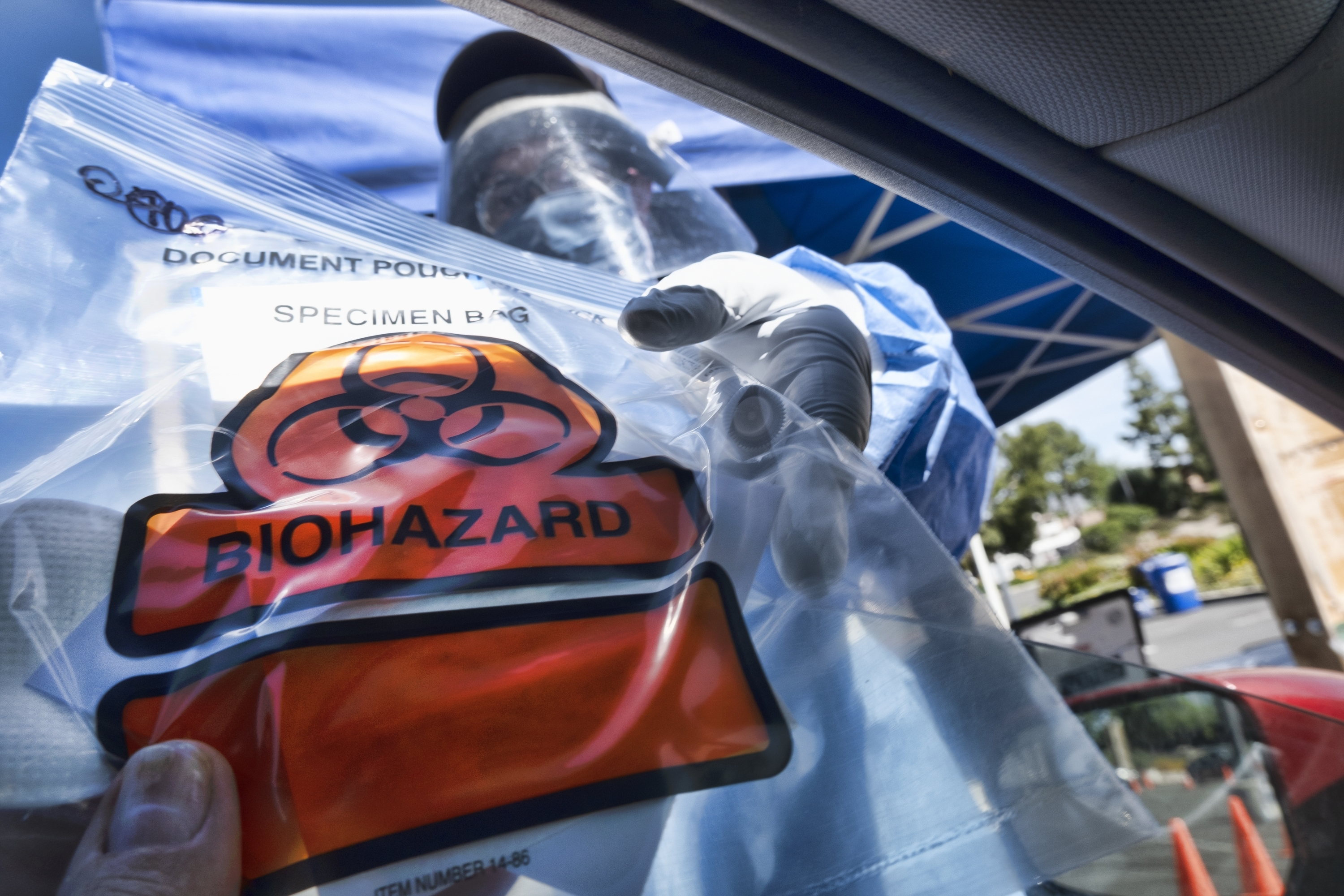 In this May 6, 2020 photo a medical worker hands a self administered coronavirus test to a patient at a drive through testing site in a parking lot in the Woodland Hills section of Los Angeles. California's death count from the coronavirus surpassed 15,000 on Sunday, Sept. 20, even as the state saw widespread improvement in infection levels.