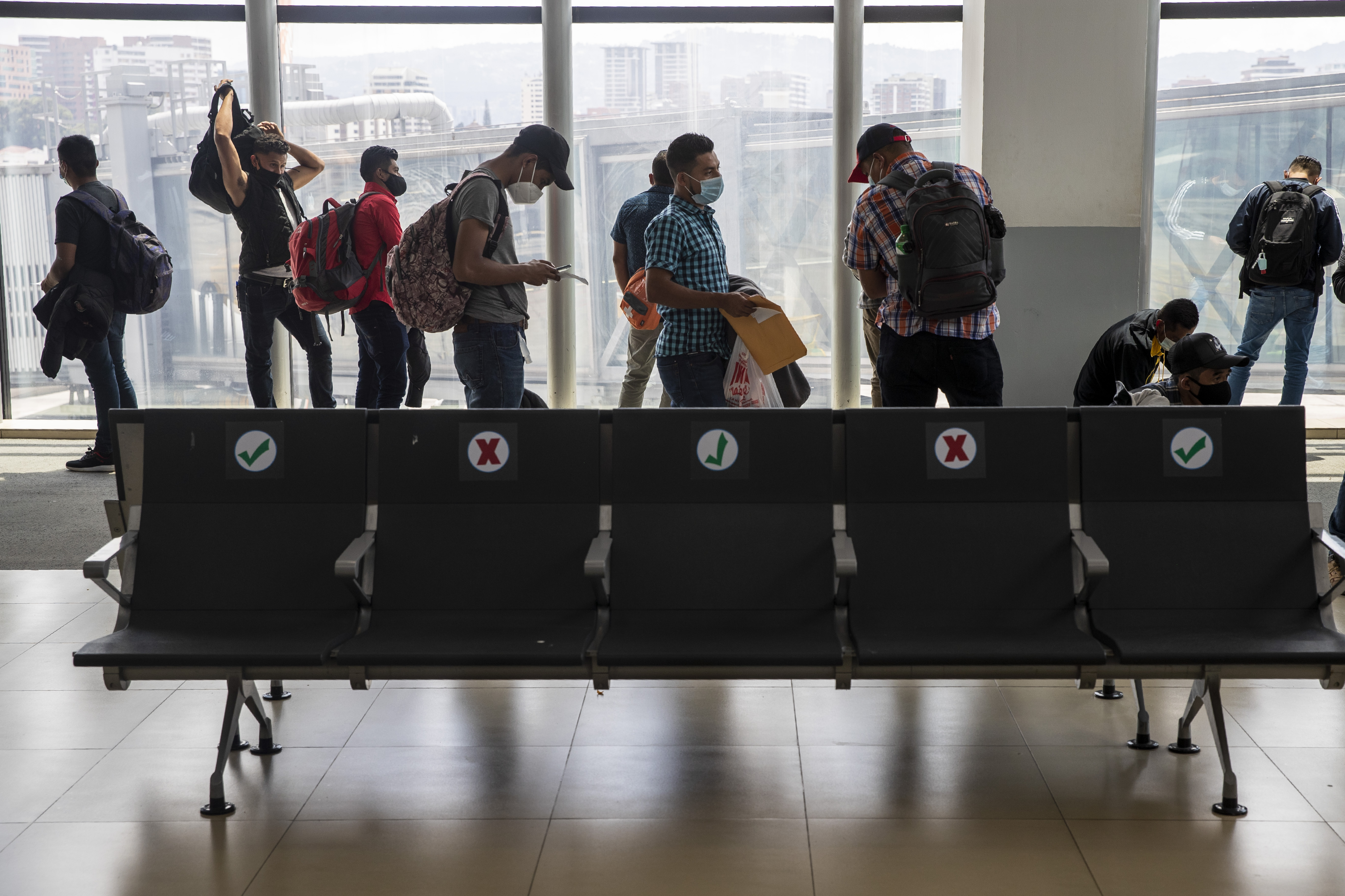 Passengers wait to board a humanitarian flight to Canada at the La Aurora international airport in Guatemala City, Thursday, Sept. 17, 2020. Authorities are preparing for the reopening of the airport on Friday as part of the gradual reopening of the country's borders by allowing national flights and some duly authorized international flights.