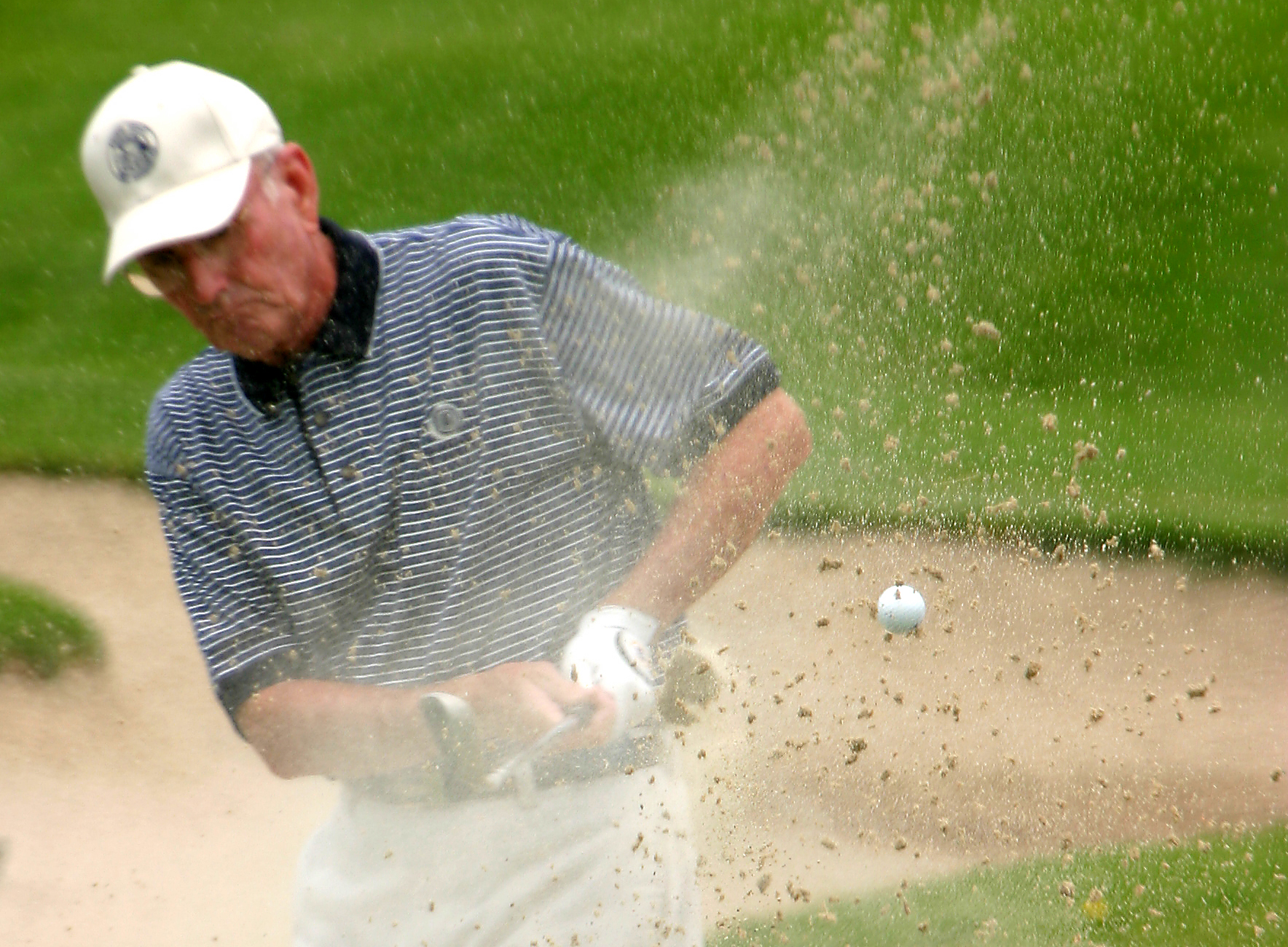 Arlen Peacock gets out of a sand trap on the eight hole of the Utah State Amateur golf tournament at the Jeremy Ranch golf course in Park City. Ryan Long/Deseret Morning News. (Submission date: 07/07/2004)