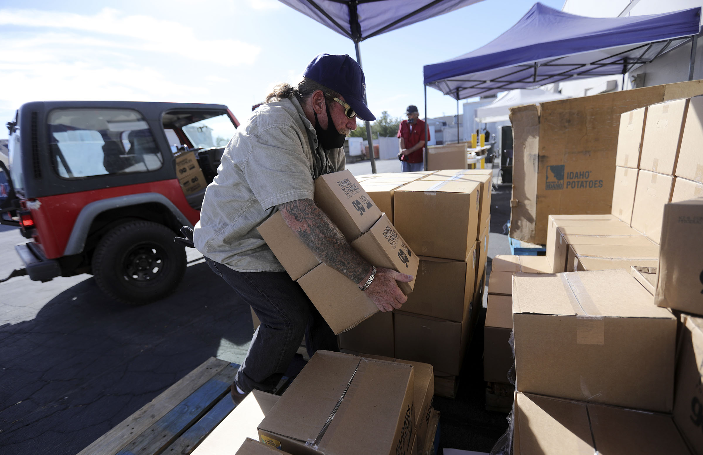 Pete Poletta loads boxes of food into a Jeep during a Take 1, Give 1 food box giveaway out outside of the Salt Lake City Mission offices in Salt Lake City on Tuesday, Oct. 13, 2020. Those who are struggling to feed their families could stop by and pick up a food box for themselves and also pick one up for a friend or neighbor in need. It was expected that 1,300 food boxes containing meat, veggies, fruit, and dairy would be given away.