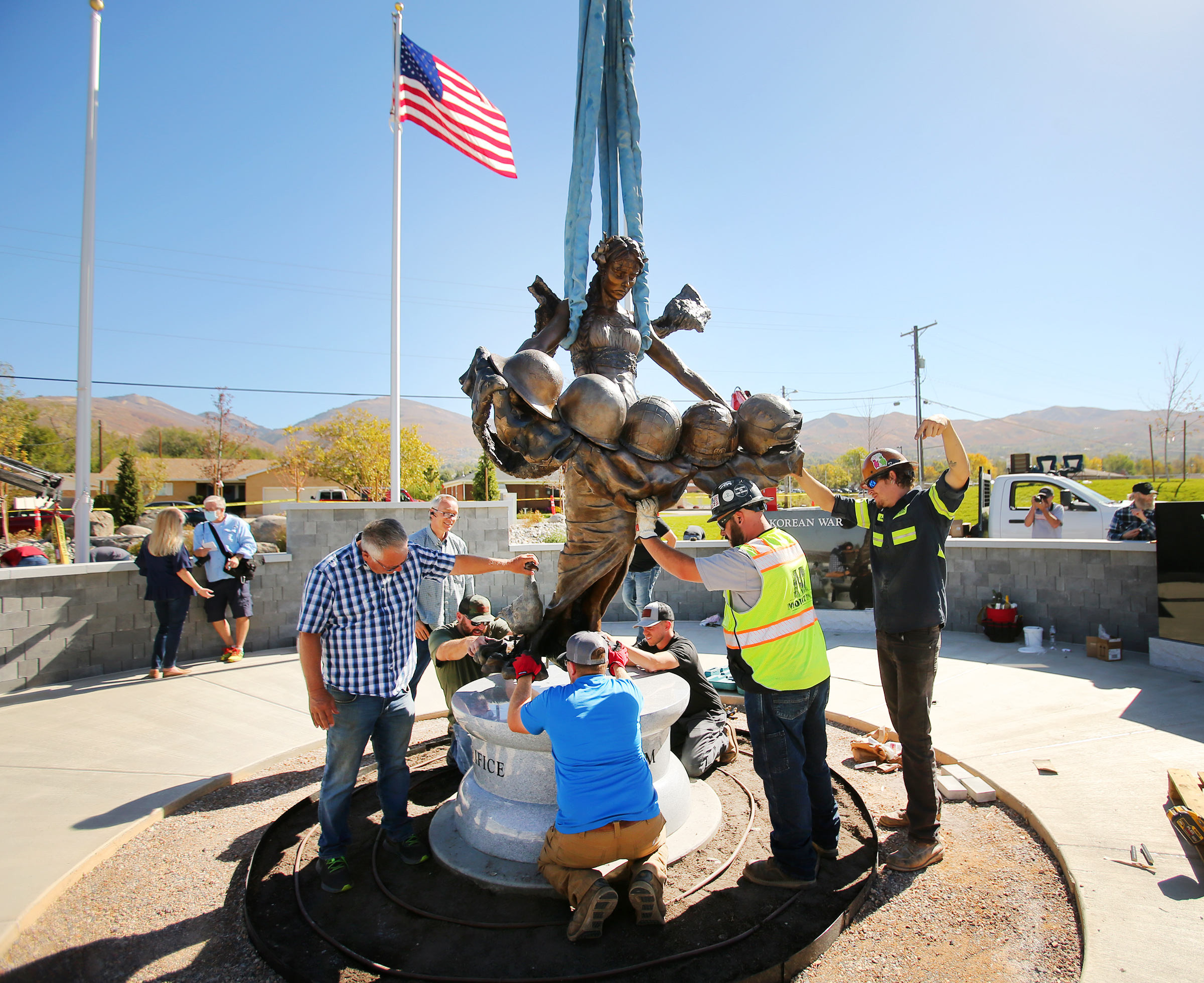 Workers install a statue of Columbia, the female personification of the United States, at Bountiful Veterans Park in Bountiful on Tuesday, Oct. 13, 2020. The 7-foot statue is surrounded by various military monuments and granite benches remembering veterans and the battles they fought.