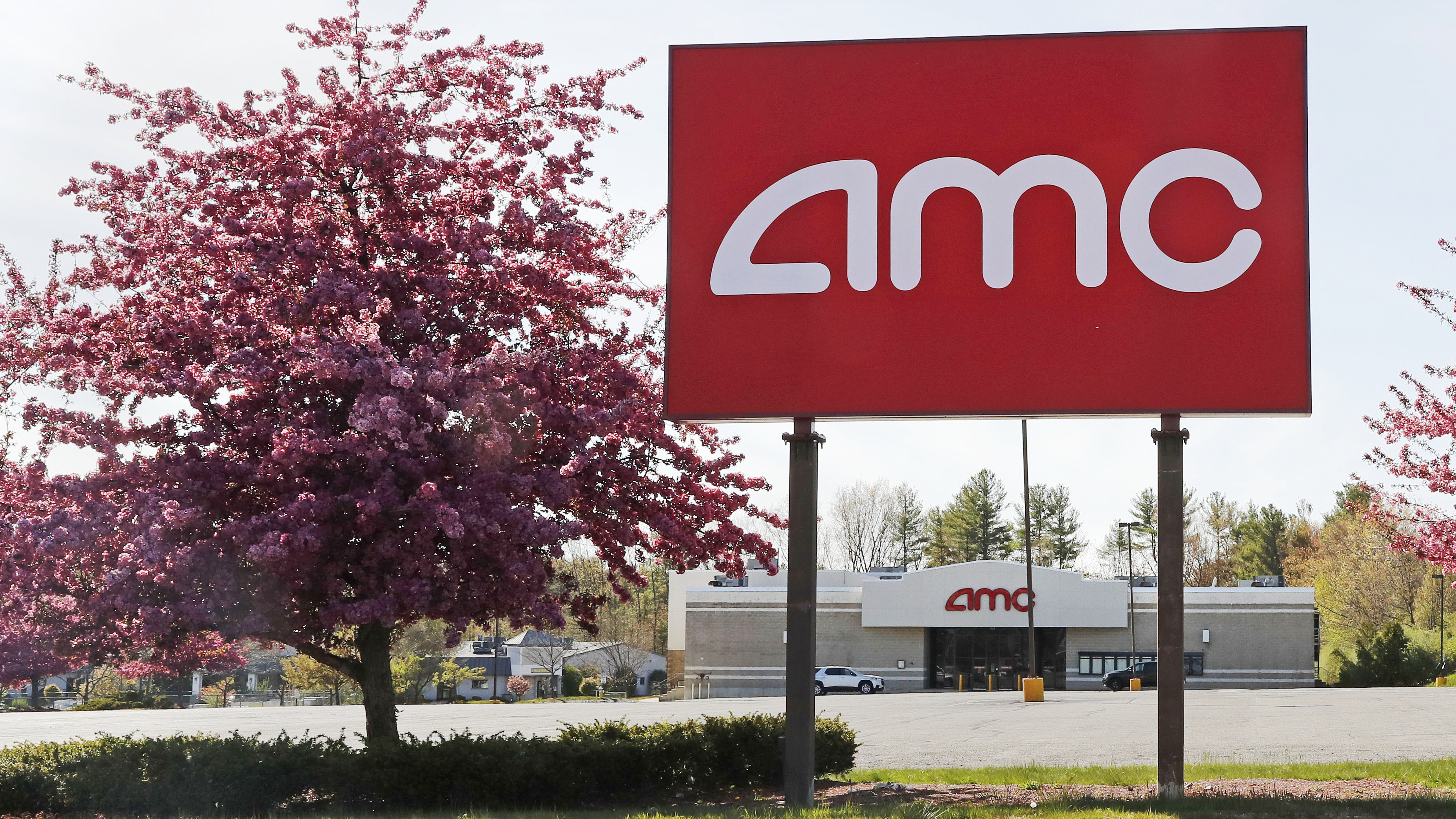 This May 14, 2020, photo shows an AMC theater sign at a nearly empty parking lot for the theater in Londonderry, N.H. After three months of near total blackout of cinemas nationwide, movie theaters are preparing to reopen - even if it means only a few titles on the marquee and showings limited to as little as 25% capacity.
