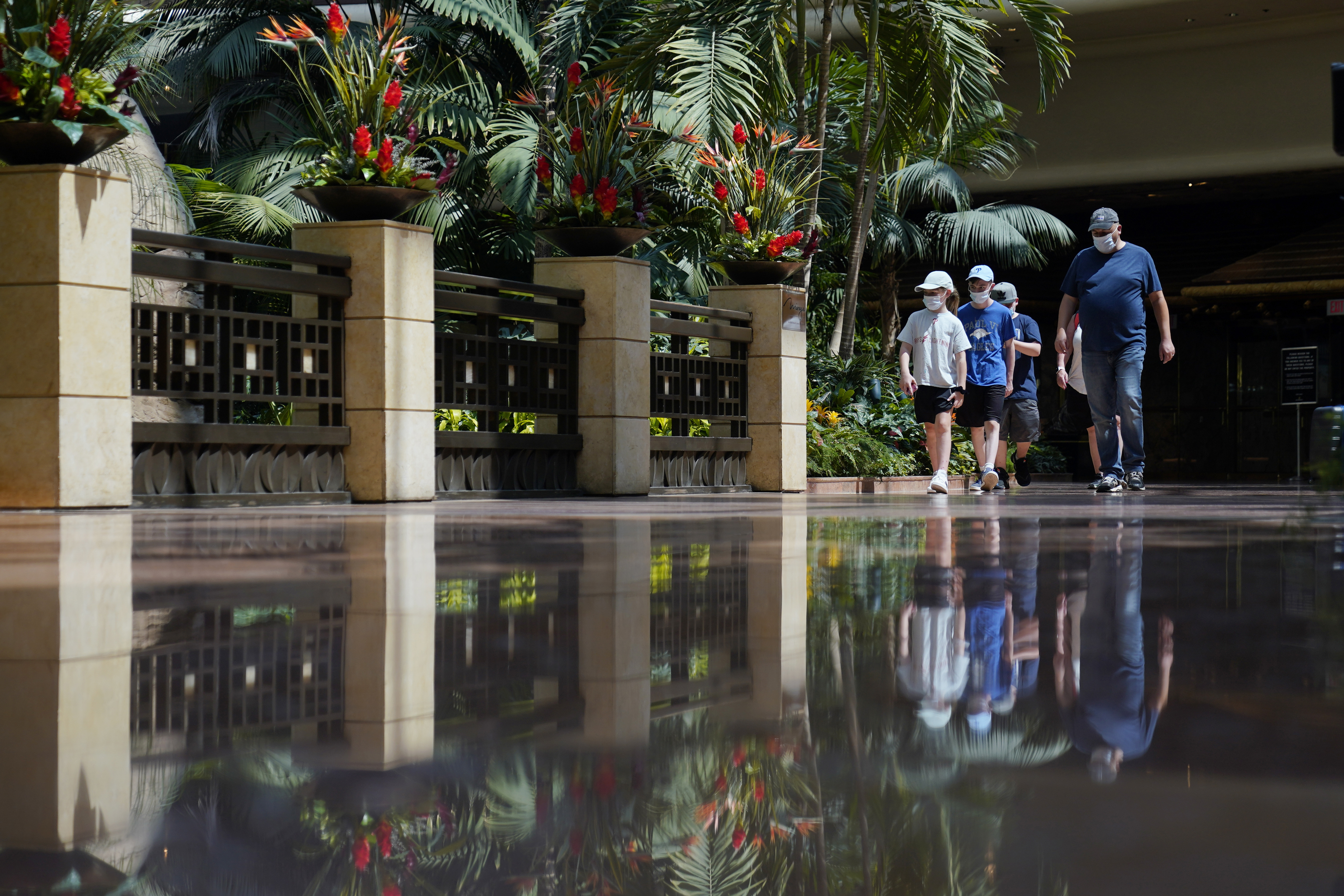 In this Aug. 27, 2020 file photo, people wearing facemasks walk through the atrium during the reopening of the Mirage hotel and casino in Las Vegas.